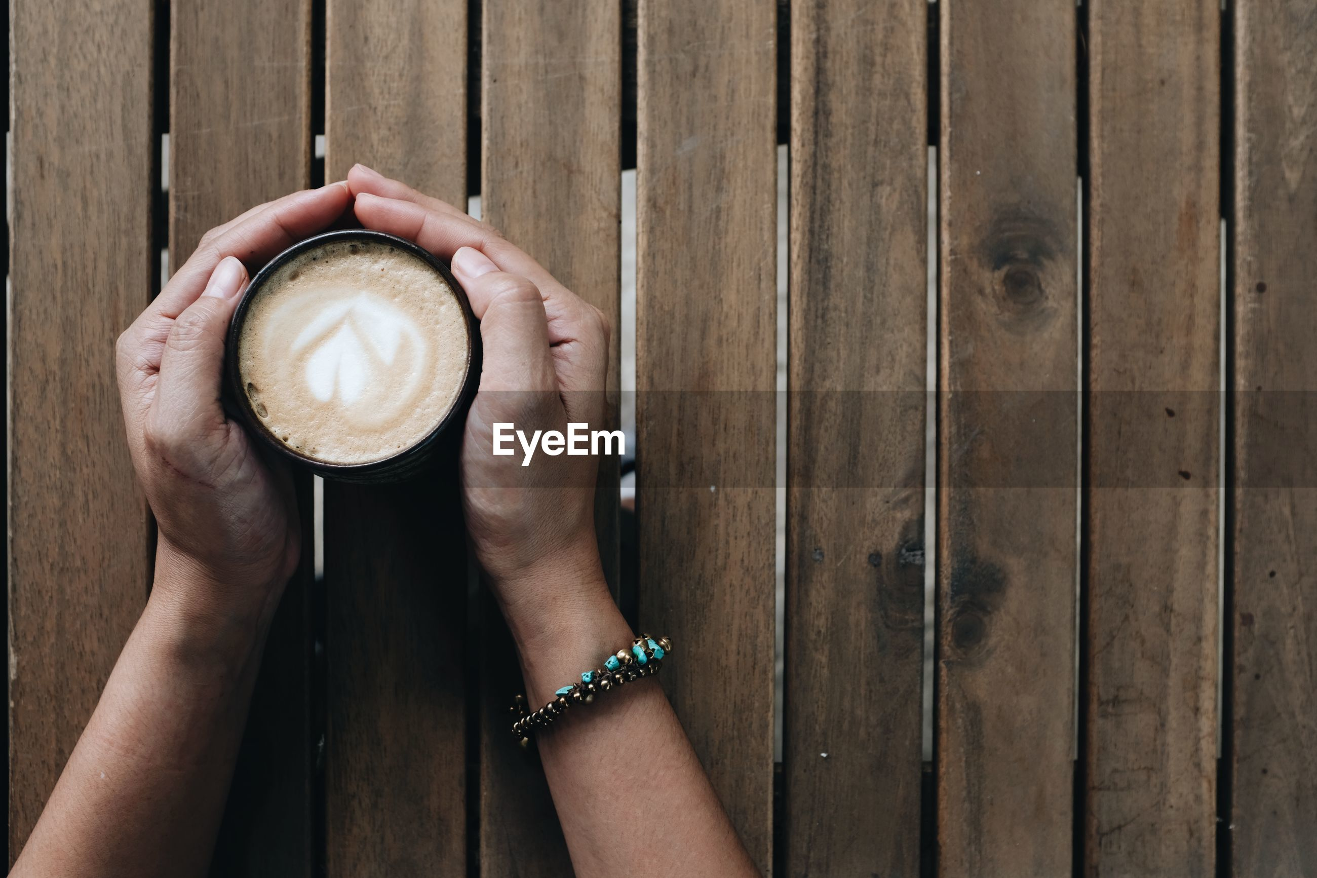DIRECTLY ABOVE SHOT OF HAND HOLDING COFFEE CUP WITH WOODEN POST