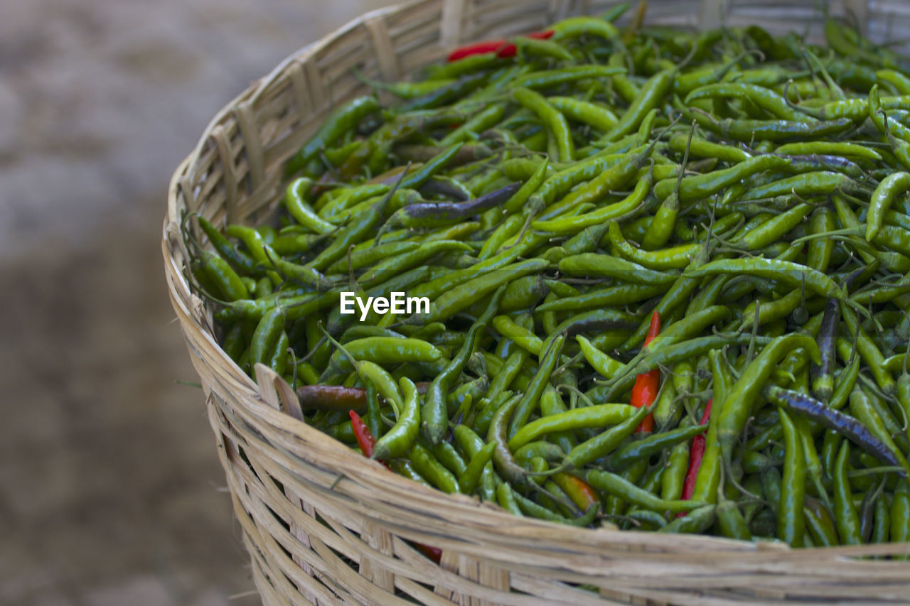Close-up of chili peppers in basket for sale at market