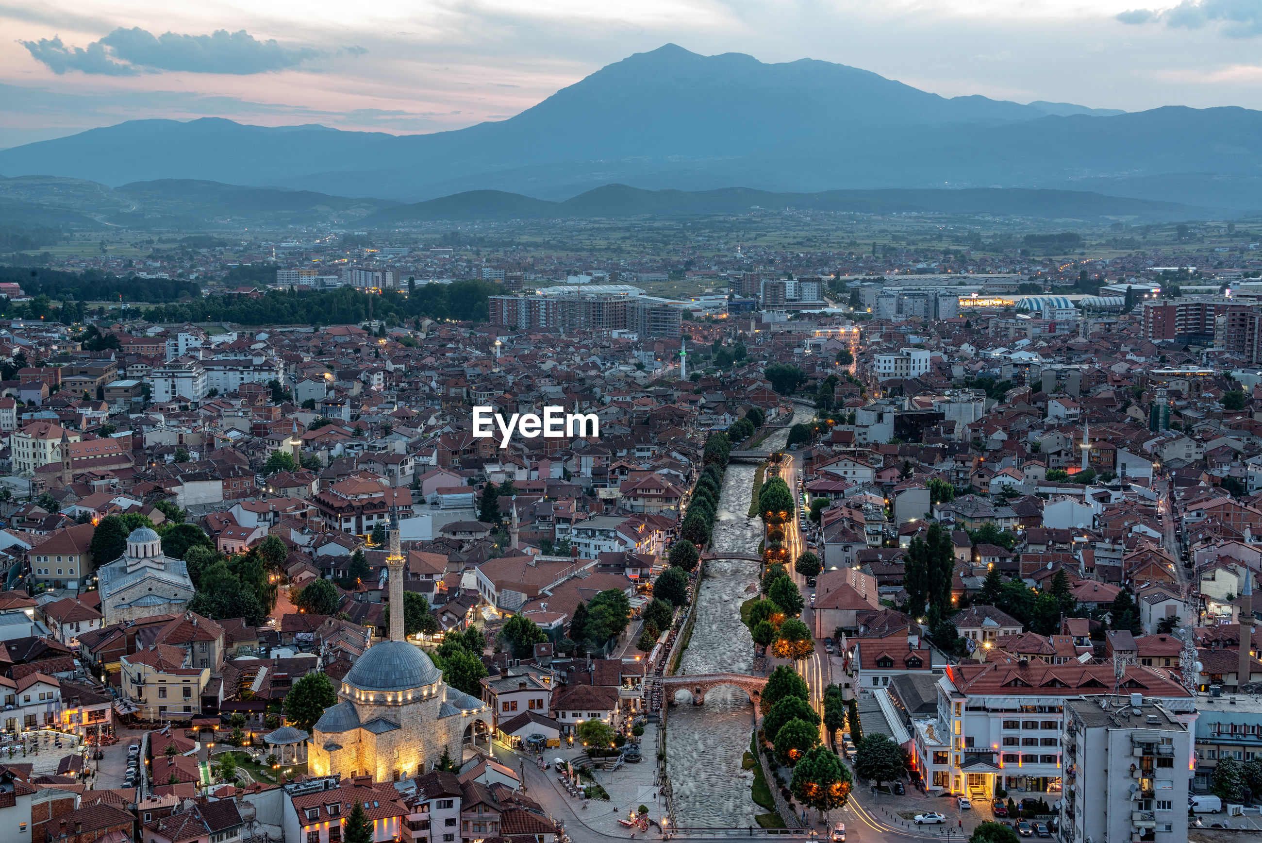 Aerial view of cityscape by mountain at dusk