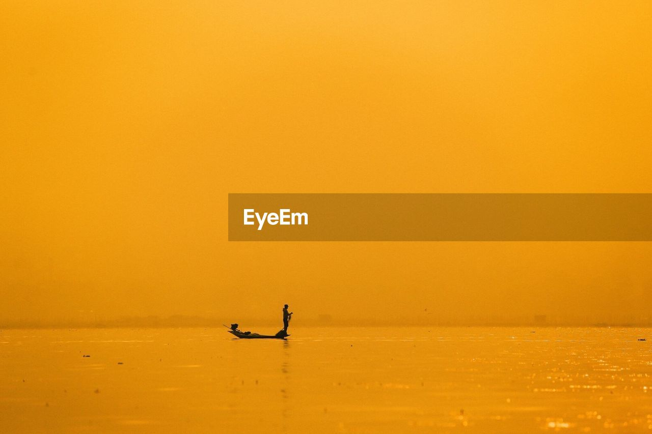 Silhouette fisherman on boat in sea against yellow sky during sunrise