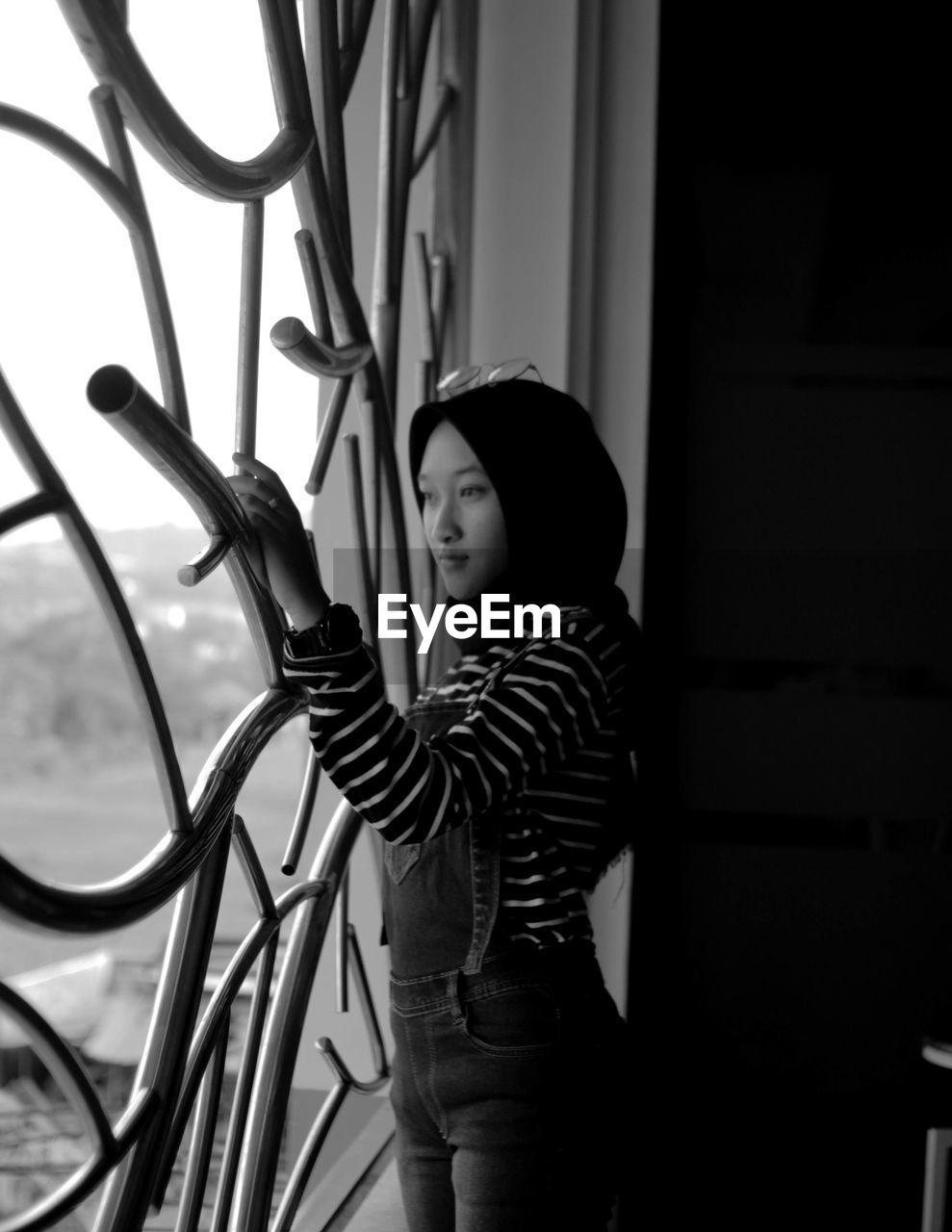 Teenage girl looking through window