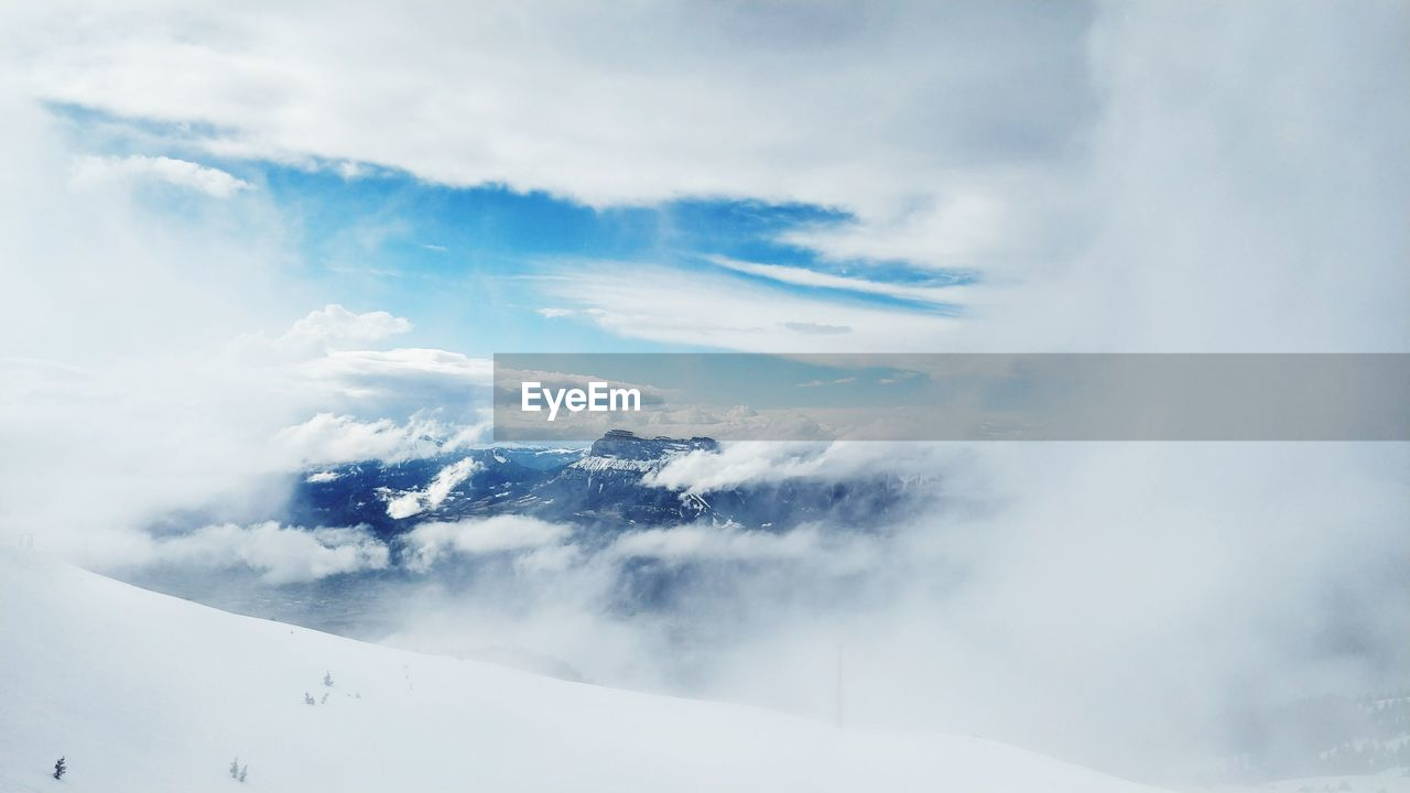 cloud - sky, sky, beauty in nature, scenics - nature, white color, tranquil scene, mountain, winter, cold temperature, nature, tranquility, day, no people, snow, non-urban scene, environment, outdoors, low angle view, travel, snowcapped mountain