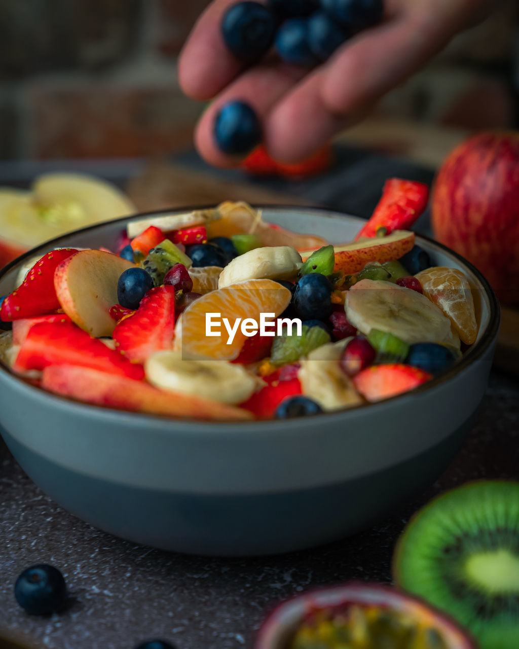 Close-up if hand adding fruit to fruit salad in bowl on table