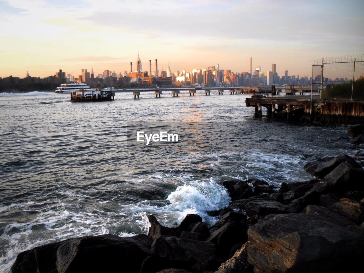 water, sky, architecture, built structure, city, building exterior, sunset, skyscraper, sea, cloud - sky, nature, urban skyline, no people, waterfront, outdoors, travel destinations, cityscape, beauty in nature, nautical vessel, day