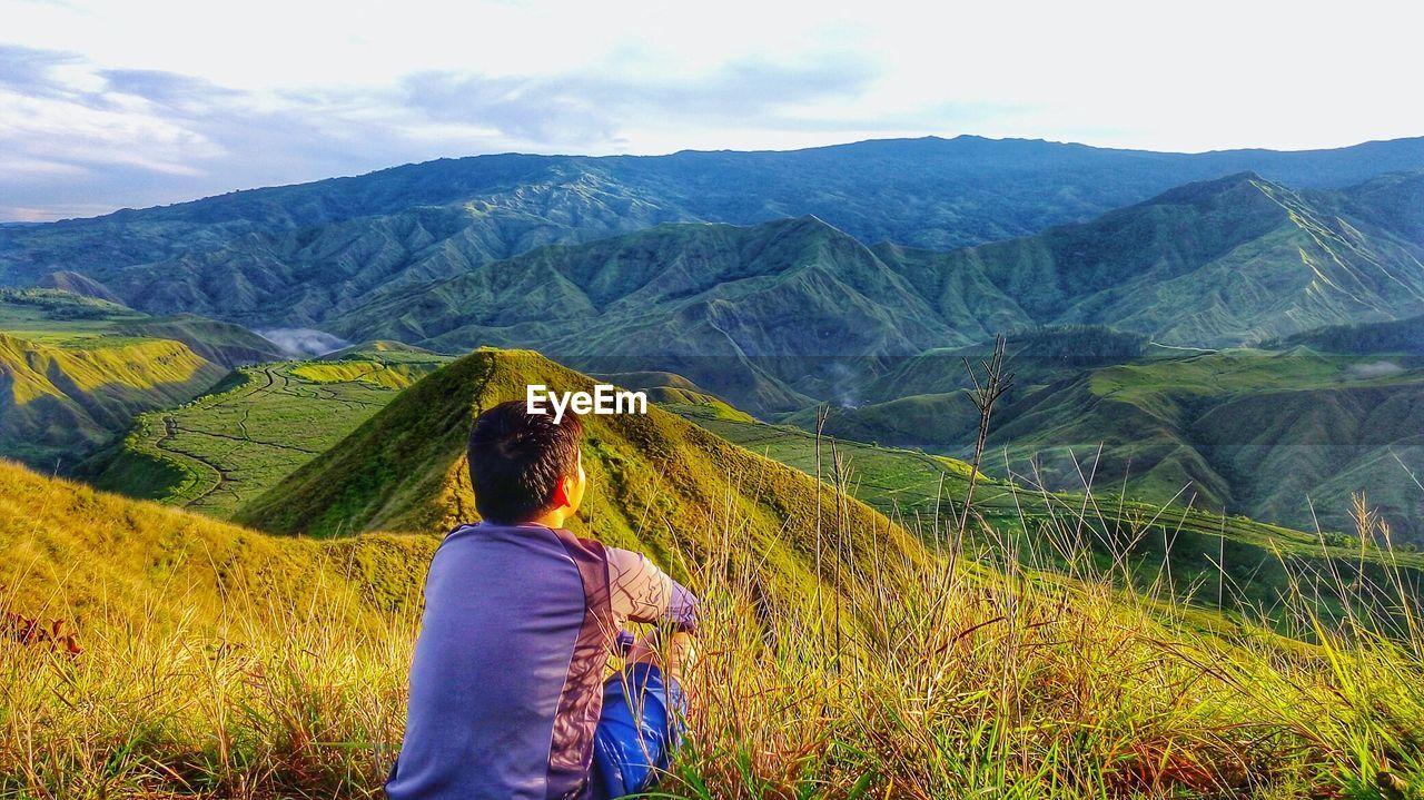 Rear view of boy sitting on mountain at panimahawa ridge
