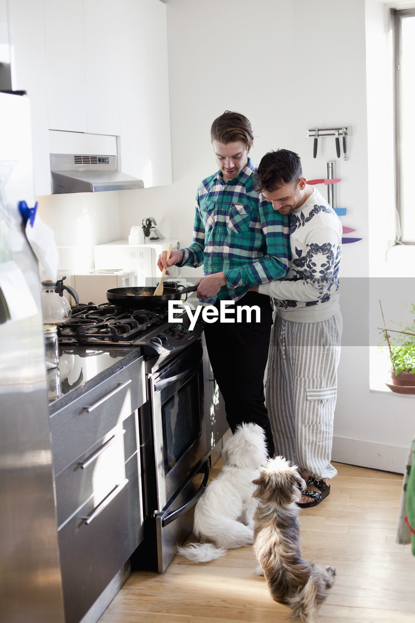 MAN AND DOG STANDING IN KITCHEN AT HOME