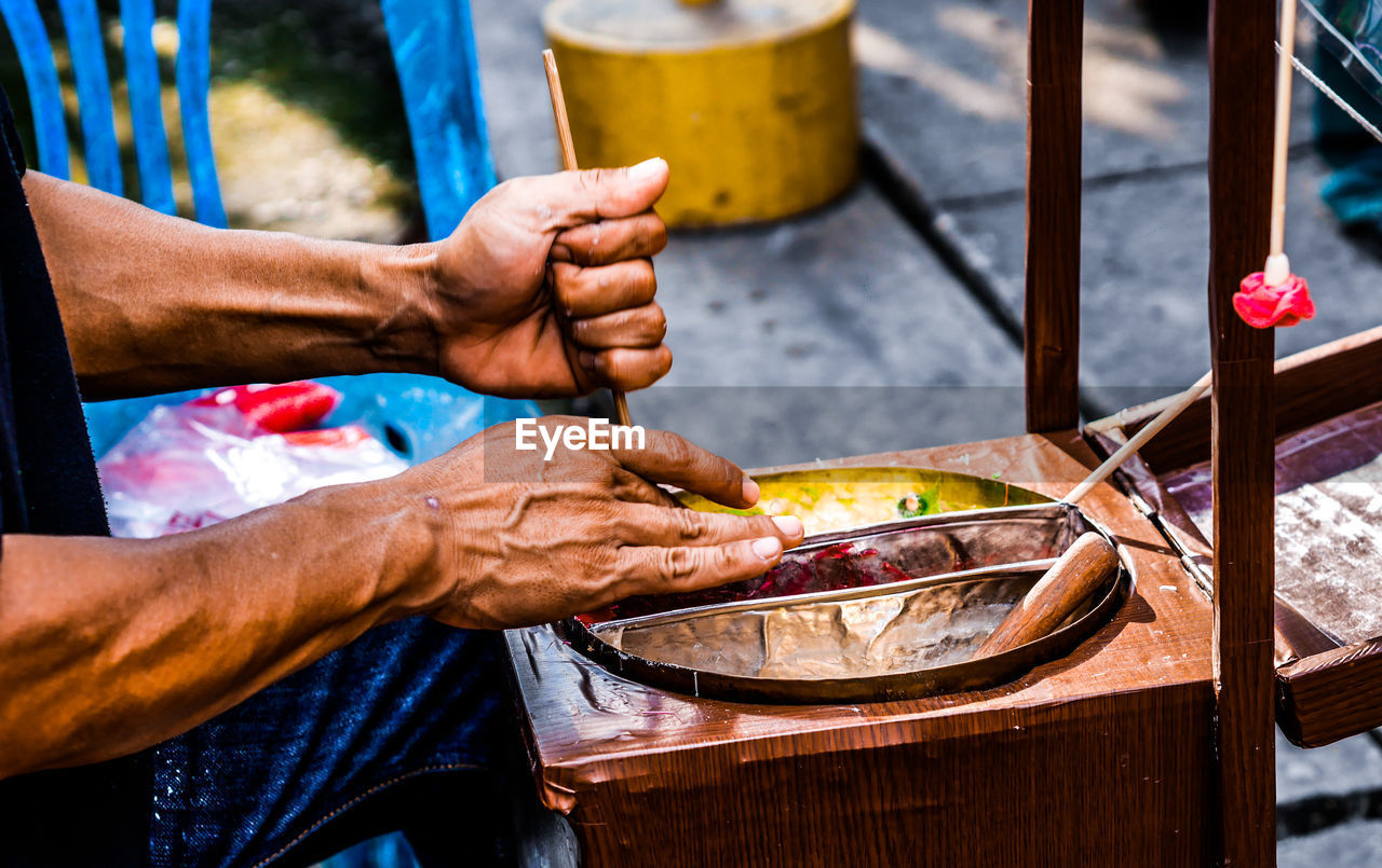 human hand, hand, food and drink, one person, real people, men, human body part, holding, food, occupation, freshness, container, focus on foreground, day, preparation, working, household equipment, vendor, midsection, outdoors, preparing food, finger