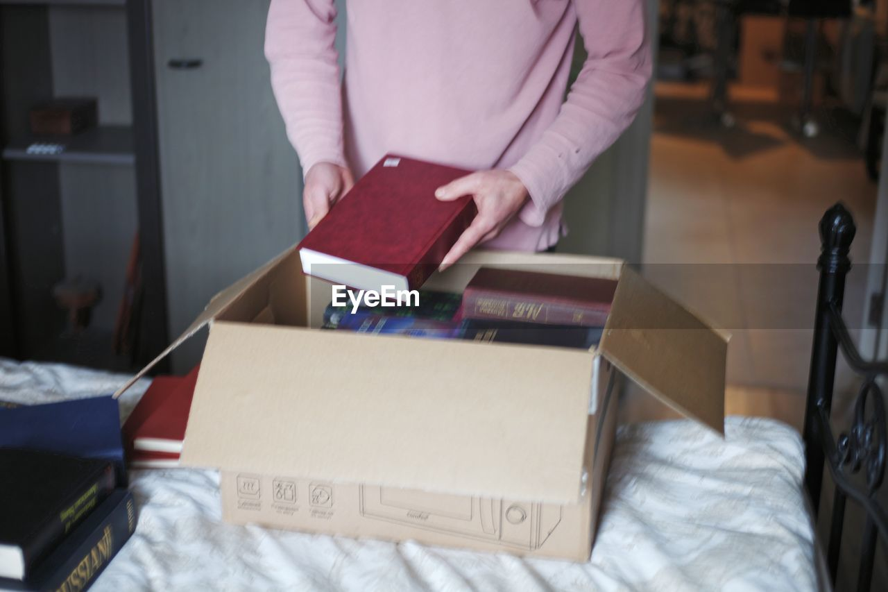 MIDSECTION OF WOMAN HOLDING BOOK WHILE STANDING AT HOME