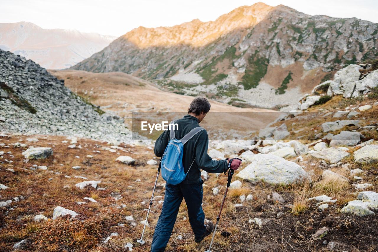 Rear view of male hiker walking on landscape