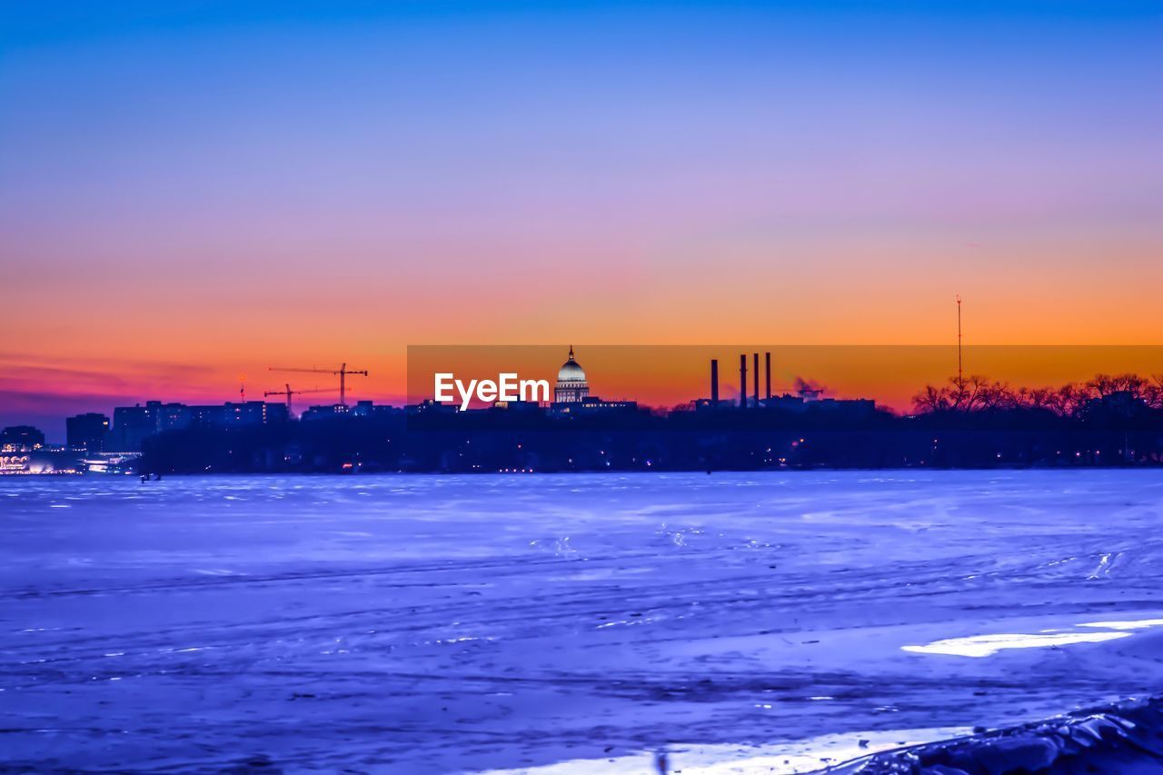 sunset, cold temperature, winter, snow, sky, nature, beauty in nature, travel destinations, no people, architecture, building exterior, built structure, outdoors, scenics, silhouette, frozen, tranquility, water, city, cityscape