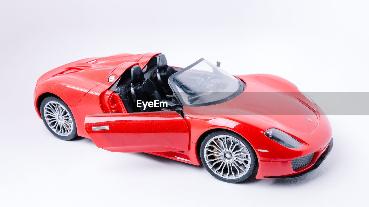 car, mode of transportation, motor vehicle, transportation, studio shot, land vehicle, white background, red, indoors, wealth, no people, cut out, still life, luxury, toy, sports car, toy car, copy space, plastic, wheel