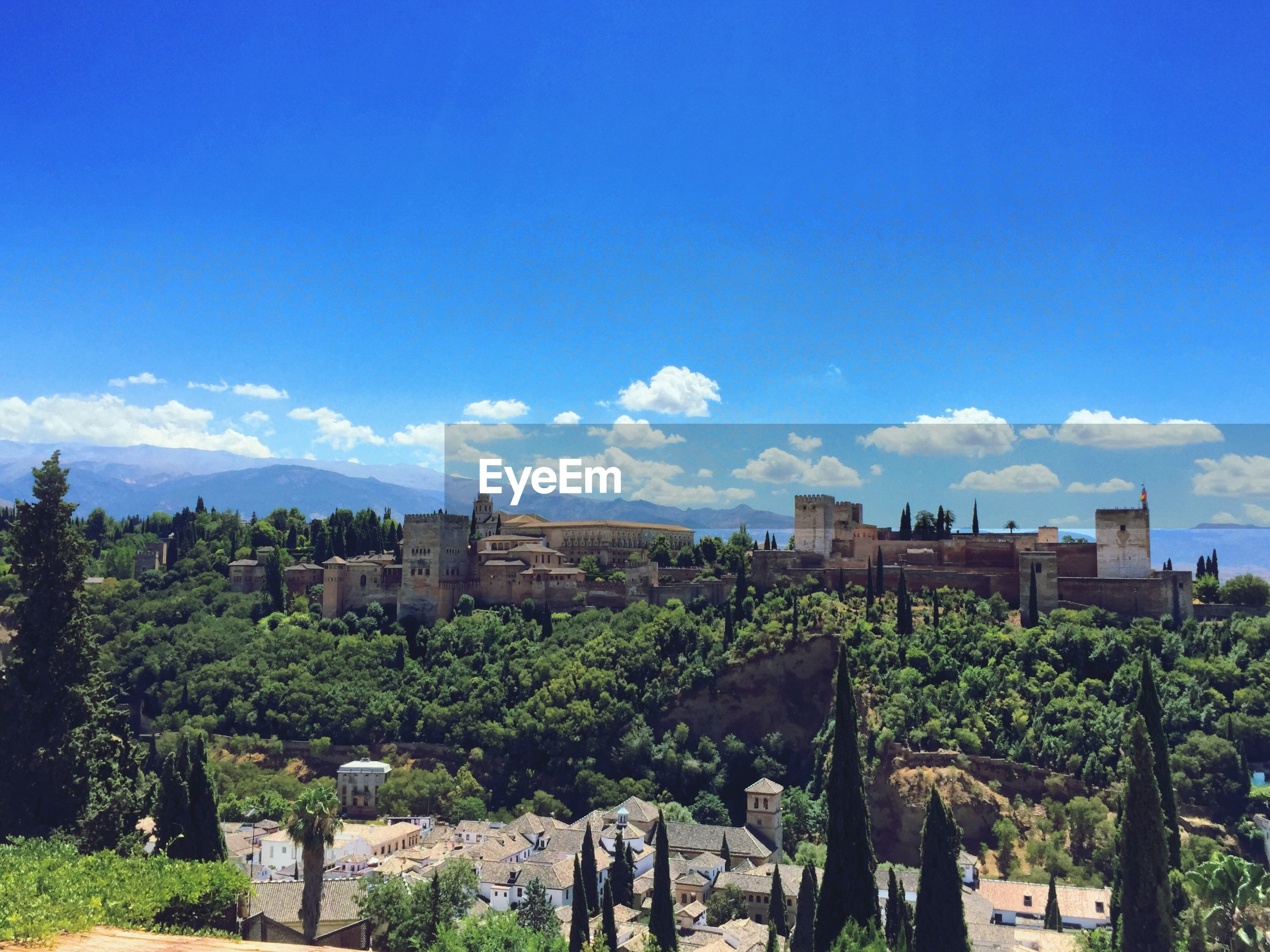 View of town against blue sky and clouds