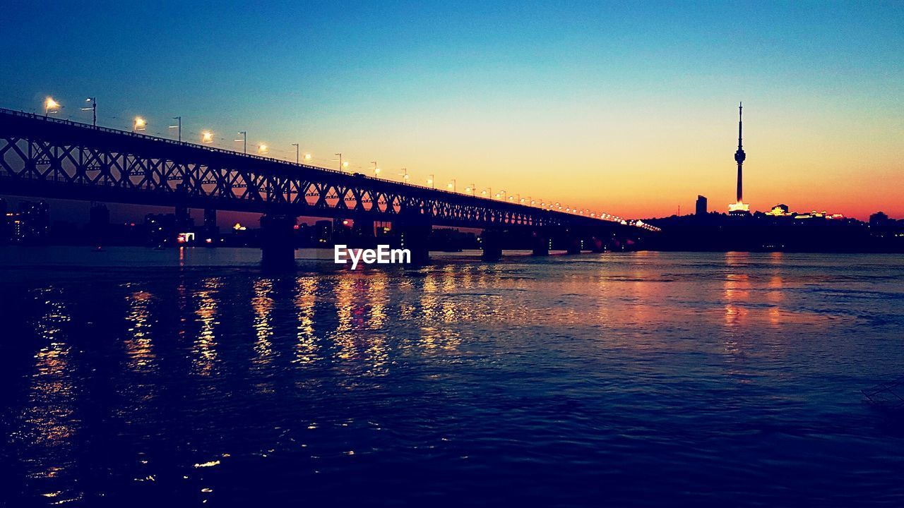 architecture, built structure, sunset, bridge - man made structure, illuminated, river, water, reflection, connection, waterfront, building exterior, silhouette, night, transportation, outdoors, sky, city, no people, clear sky, nature