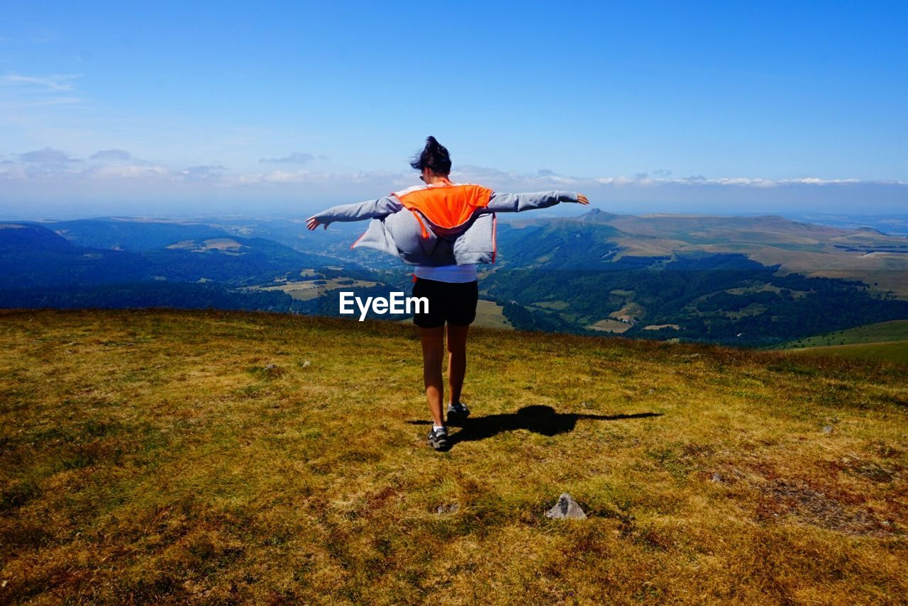 Rear view of woman with arms outstretched on mountain against blue sky