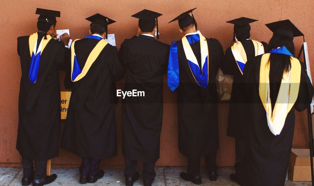 Rear View Of Students In Mortarboards Writing On Paper Against Wall