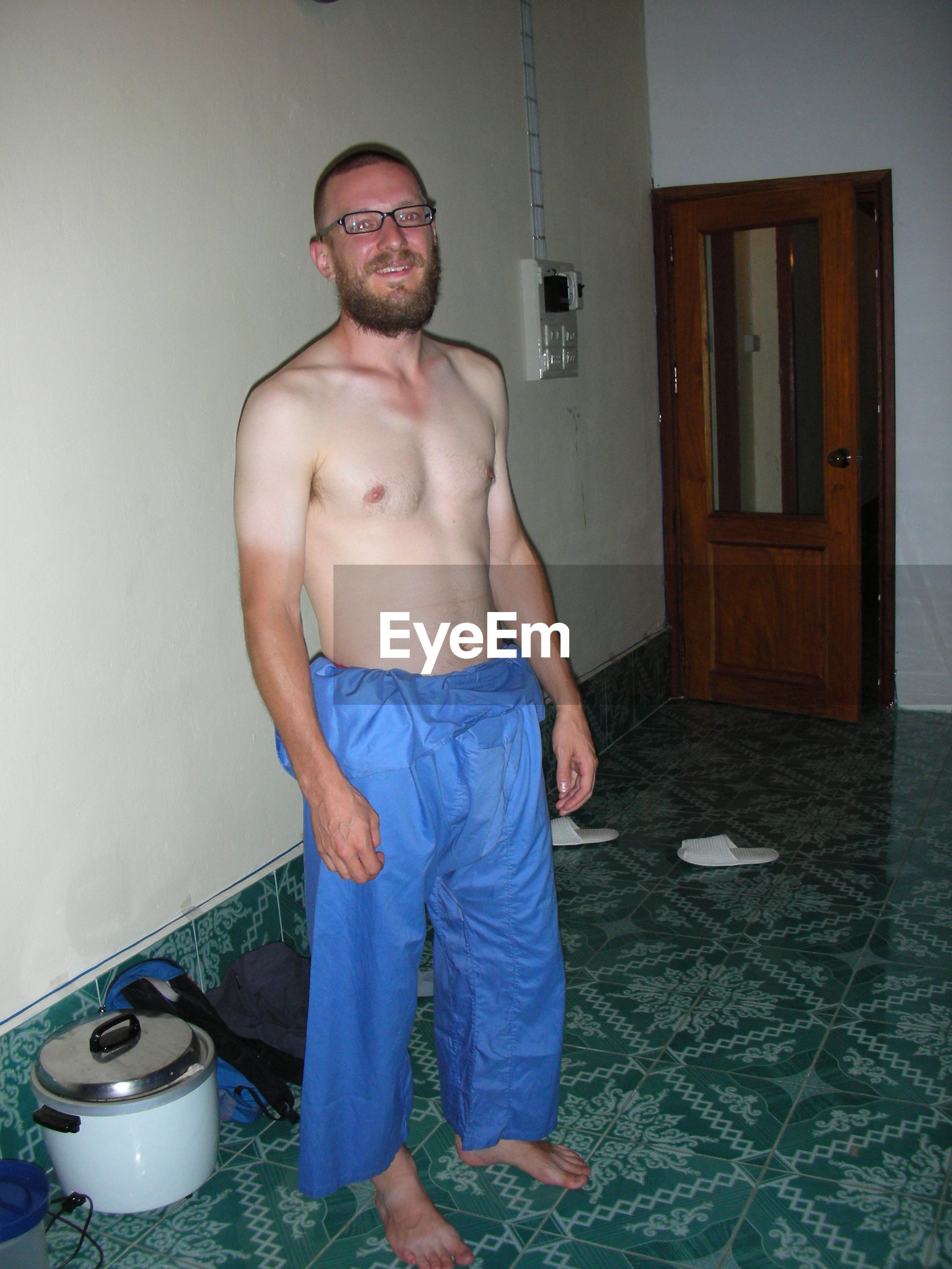 Portrait of smiling shirtless young man standing at home