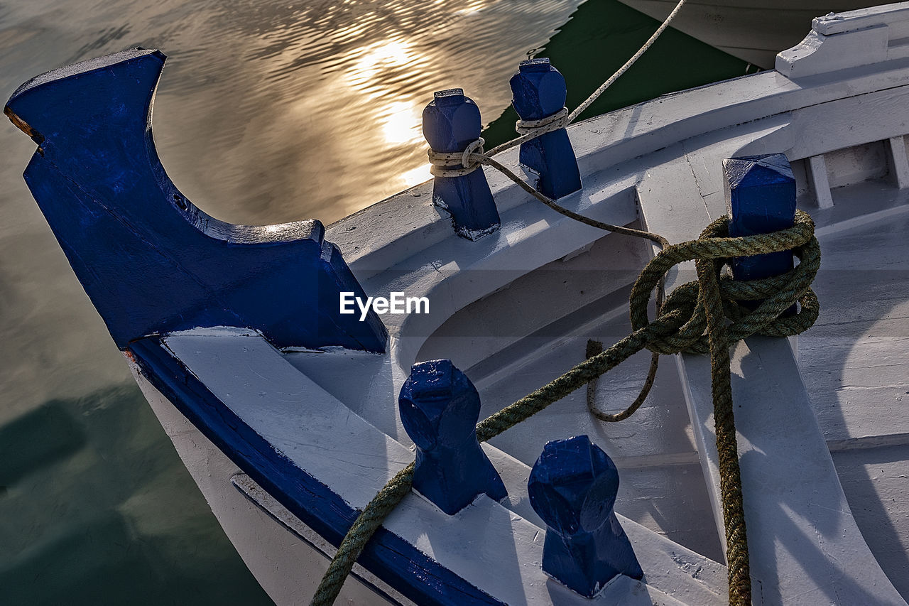 water, nautical vessel, high angle view, moored, rope, mode of transportation, nature, blue, transportation, day, sea, no people, outdoors, post, wood - material, reflection, tied up, fishing boat, wooden post