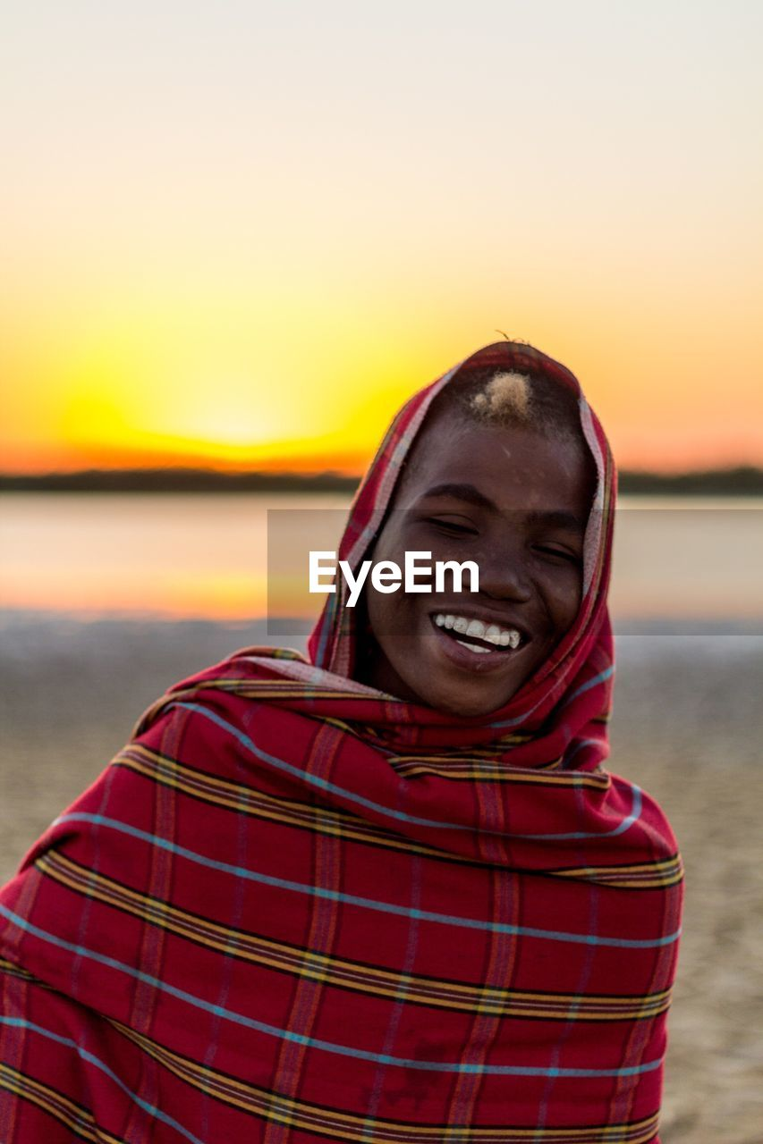 PORTRAIT OF SMILING MAN AGAINST SCENIC SKY
