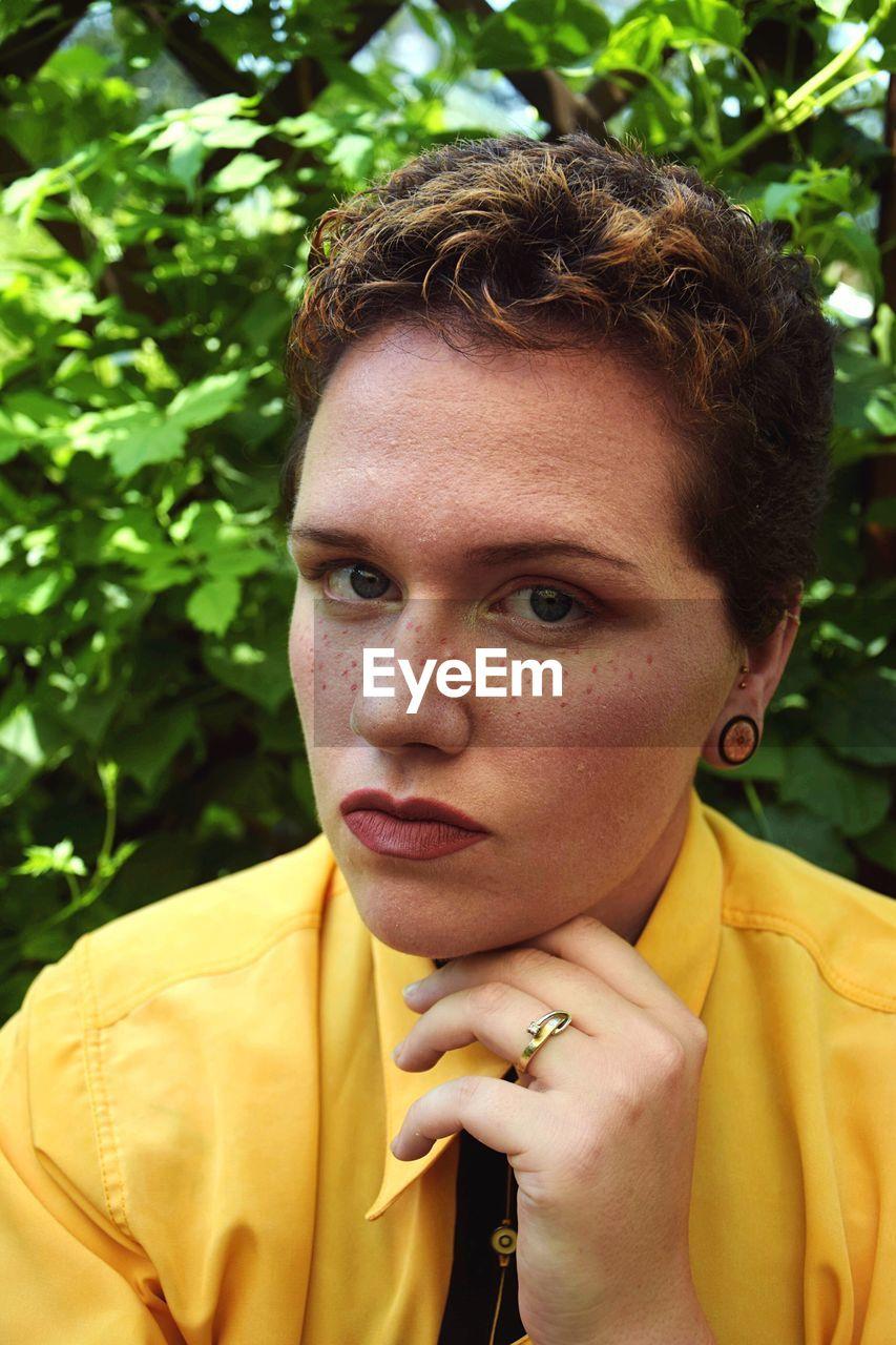 Portrait of hipster woman against plants