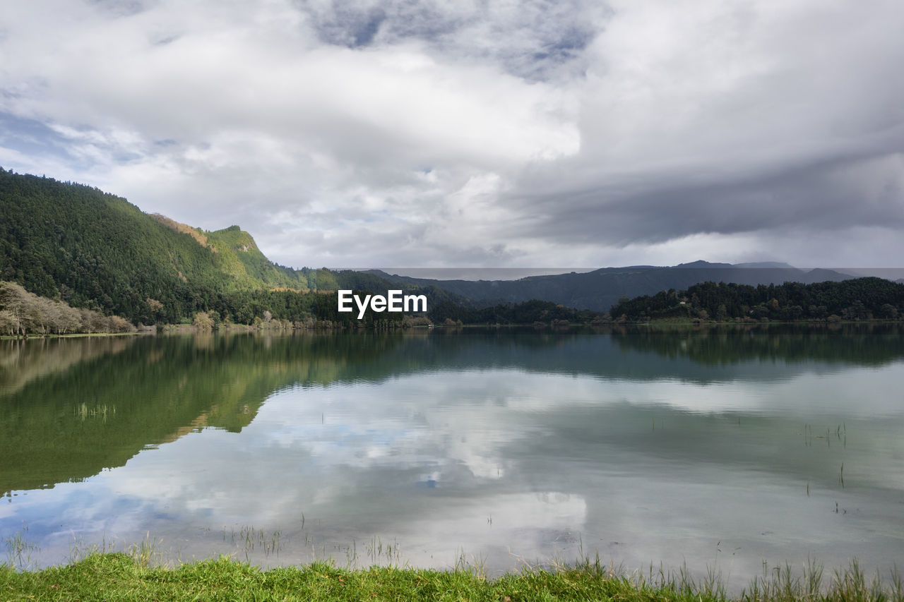 water, cloud - sky, sky, lake, tranquility, reflection, tranquil scene, beauty in nature, scenics - nature, mountain, non-urban scene, nature, idyllic, day, no people, plant, environment, tree, outdoors, reflection lake