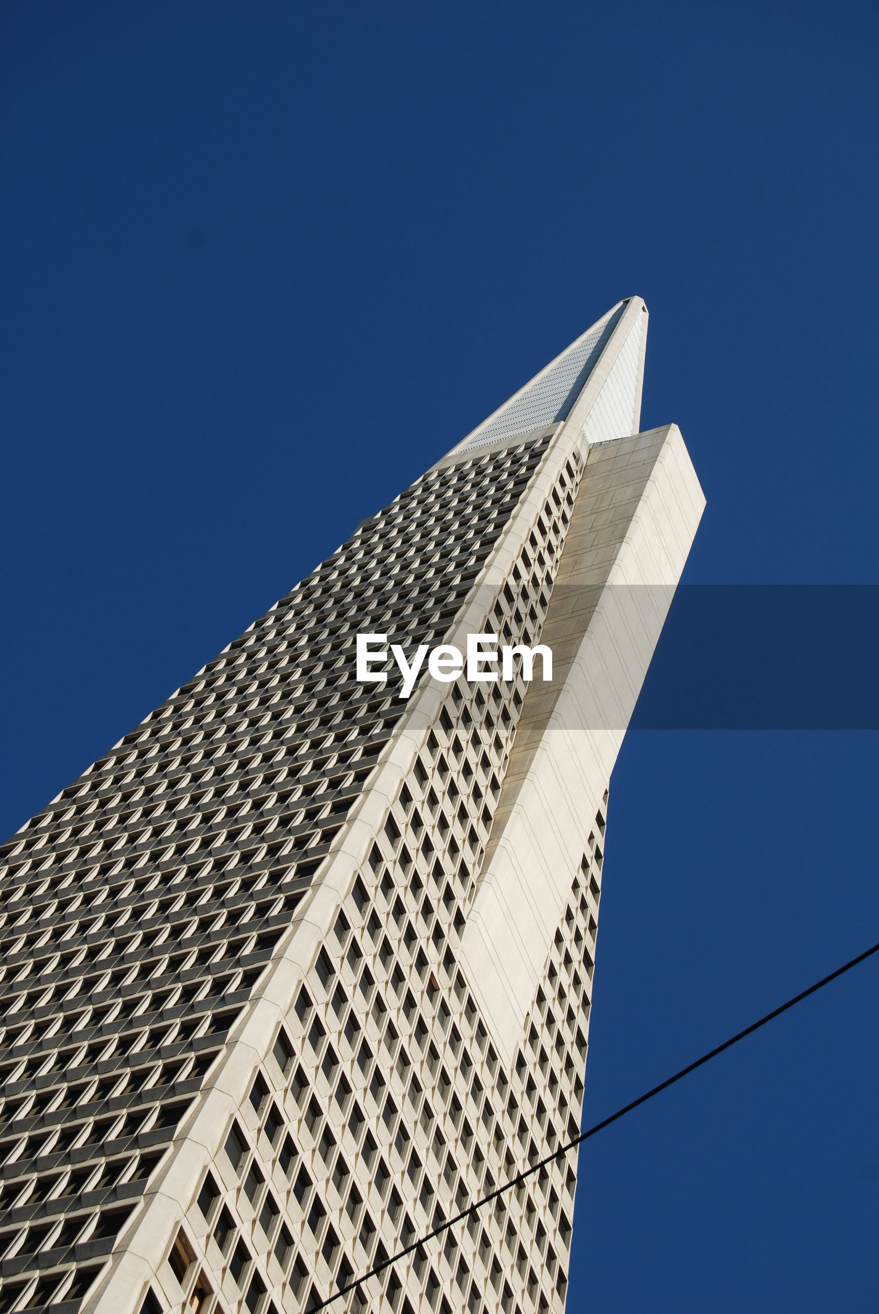 low angle view, clear sky, blue, copy space, architecture, built structure, building exterior, modern, no people, day, outdoors, sky, building, tall - high, high section, communication, city, part of, tower, skyscraper
