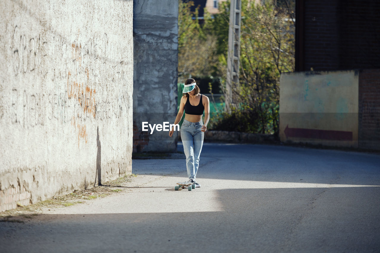 Full length of young woman skateboarding on street
