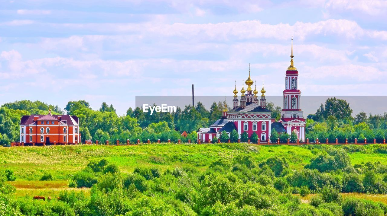 architecture, building exterior, built structure, sky, plant, building, cloud - sky, nature, green color, field, tree, place of worship, religion, belief, land, landscape, grass, travel destinations, spirituality, growth, no people, outdoors, spire