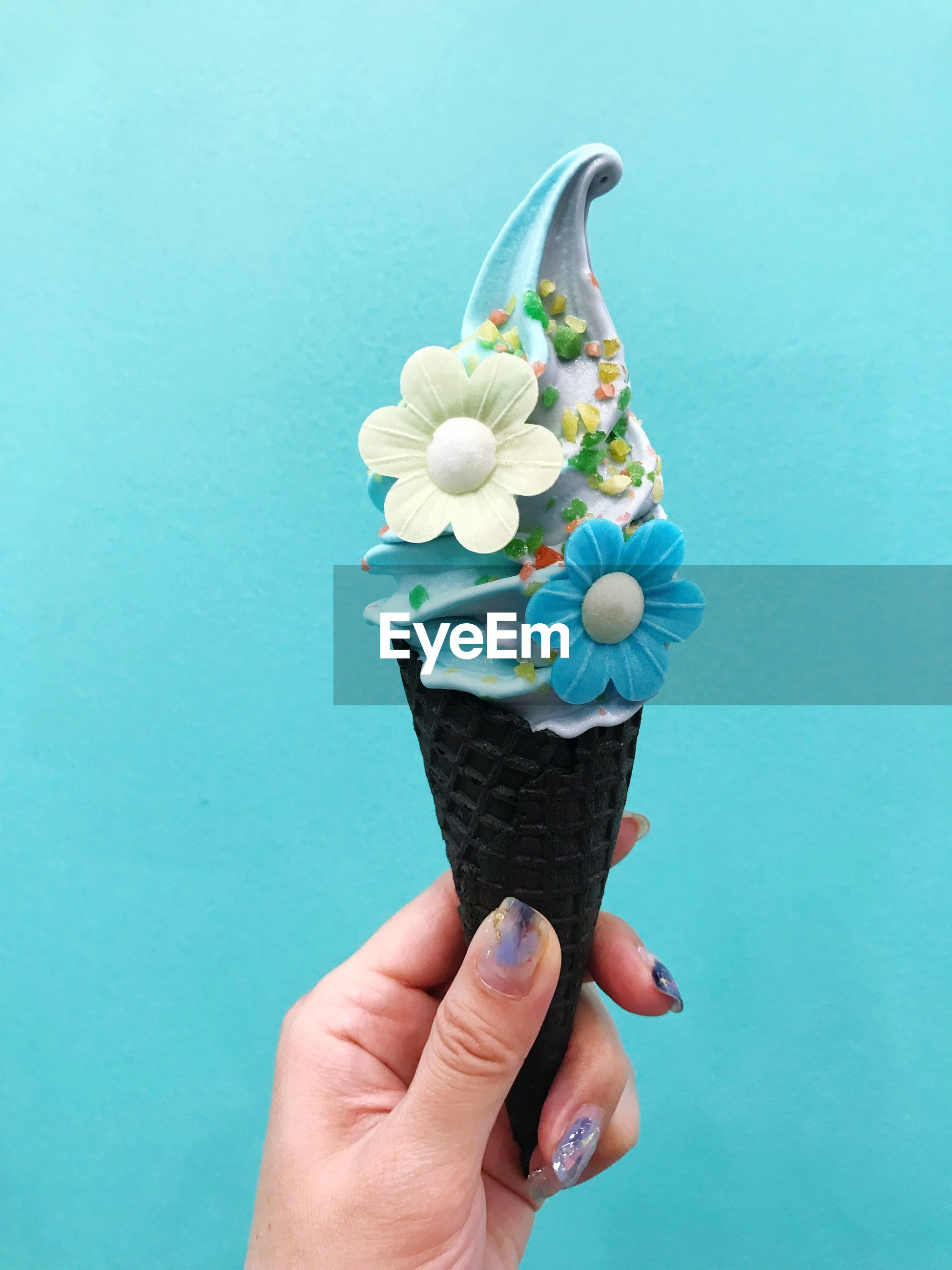 Close-up of hand holding ice cream against blue background