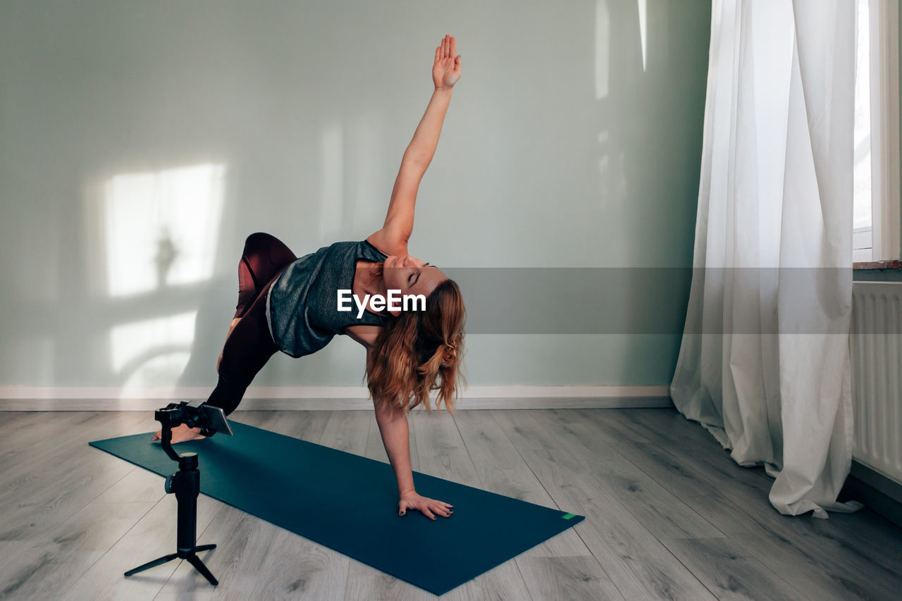 Yoga teacher connected from home broadcasting lesson via social media using smartphone on gimbal