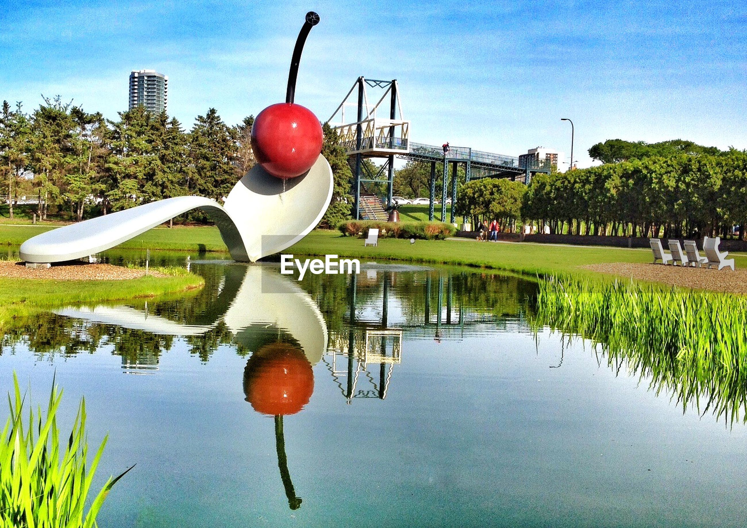 water, tree, reflection, mid-air, sky, waterfront, transportation, lake, buoy, river, built structure, balloon, building exterior, mode of transport, outdoors, architecture, nature, hanging, grass, day