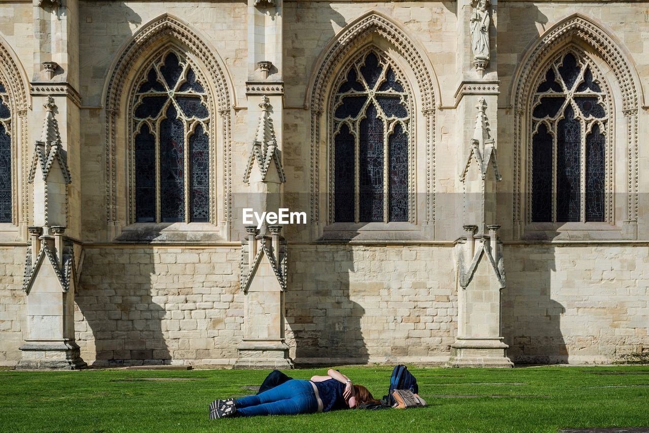 Man And Woman Romancing On Grass Outside Gloucester Cathedral