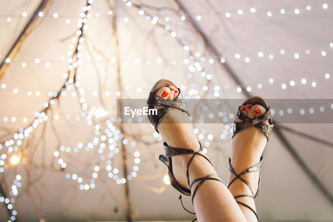 Low Section Of Woman Wearing Heels With Feet Up Against Illuminated Lights