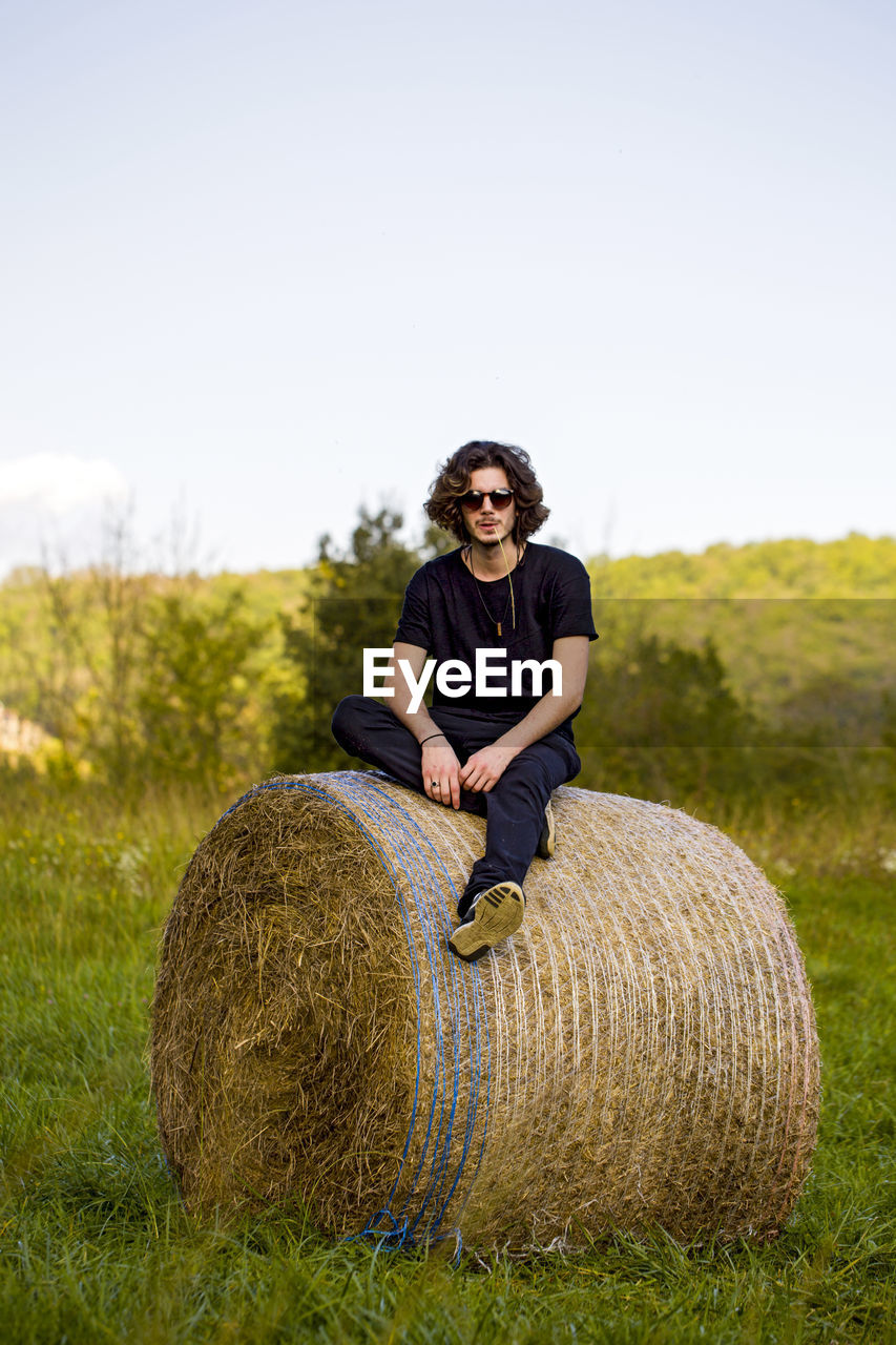 Portrait Of Man Sitting On Hay Bale Against Sky