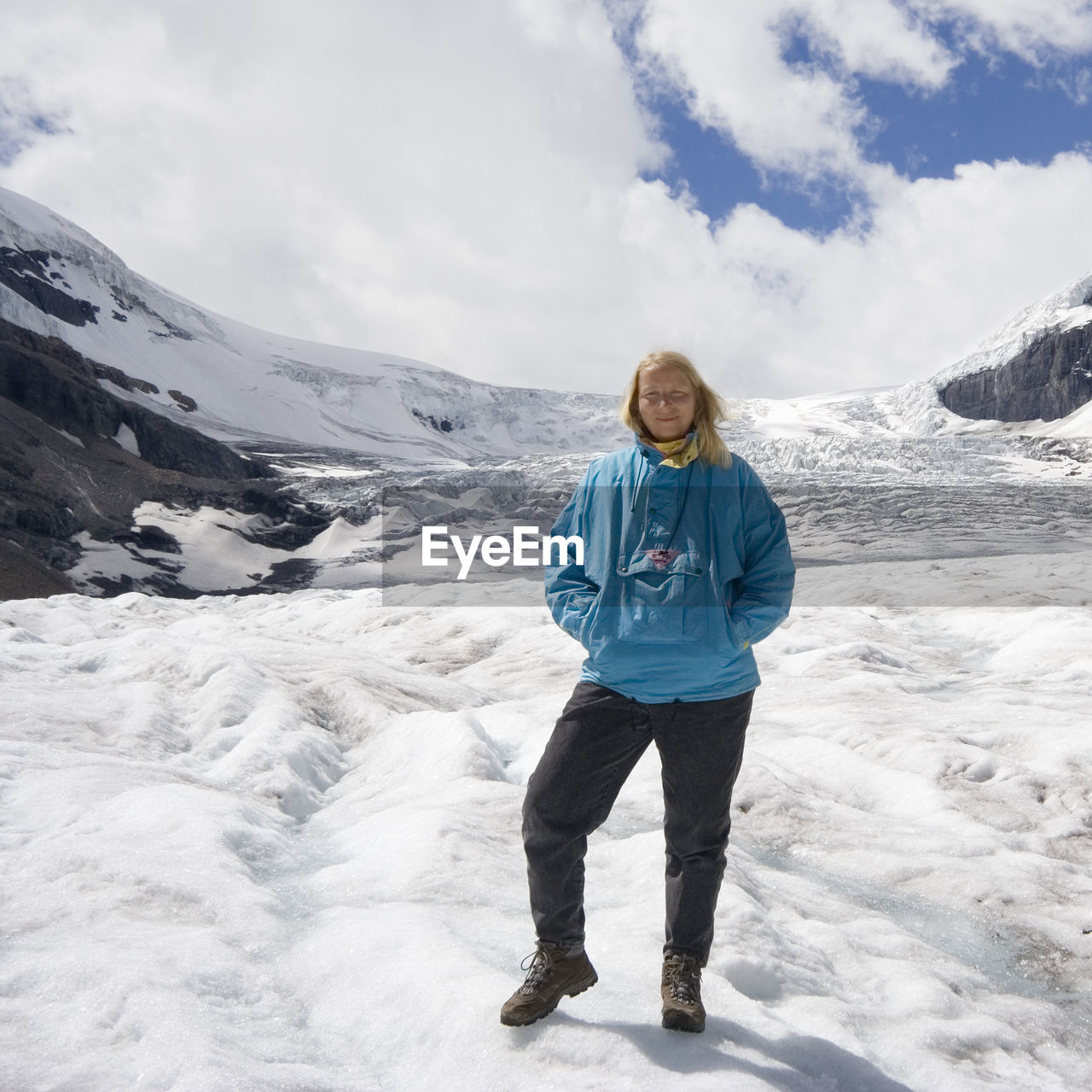 Full Length Of Woman Standing At Athabasca Glacier Against Sky