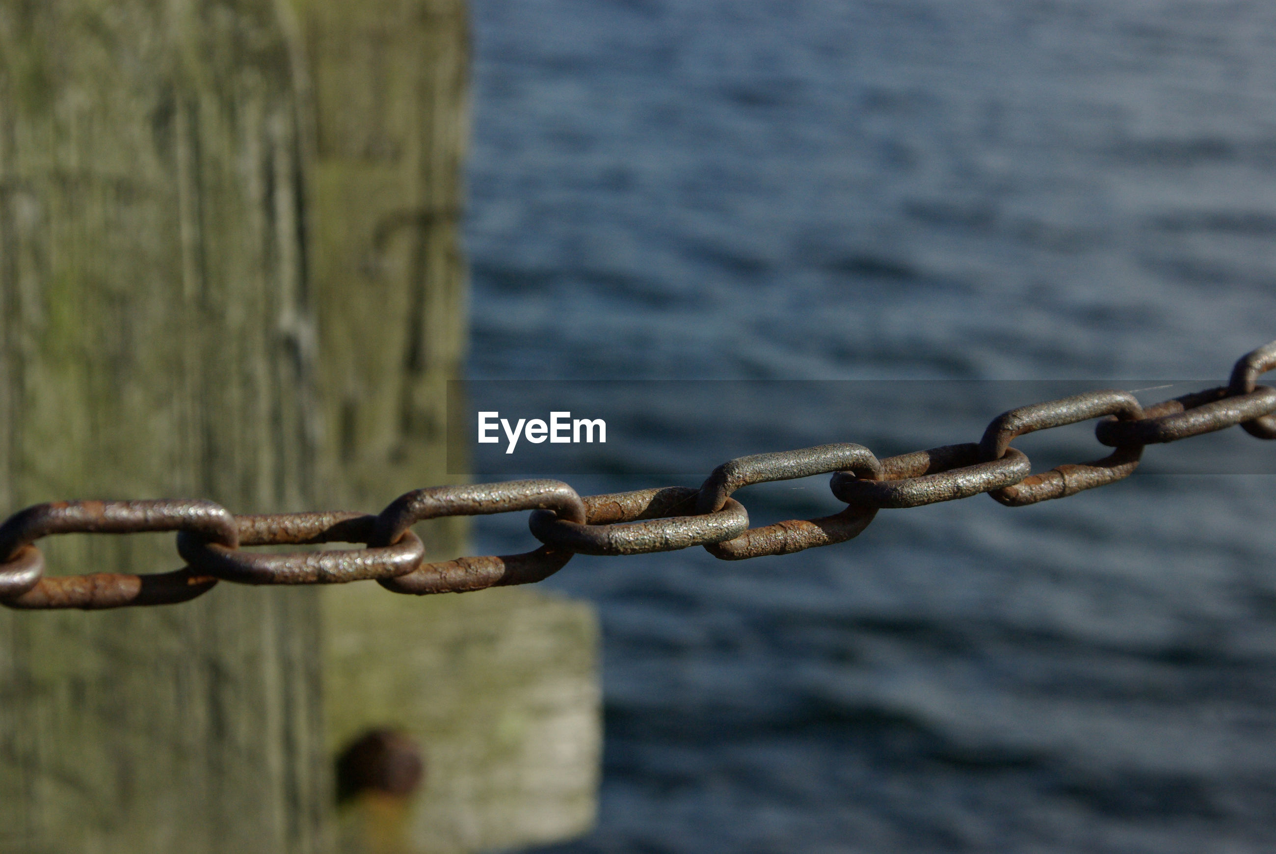 Close-up of chain on pier against sea