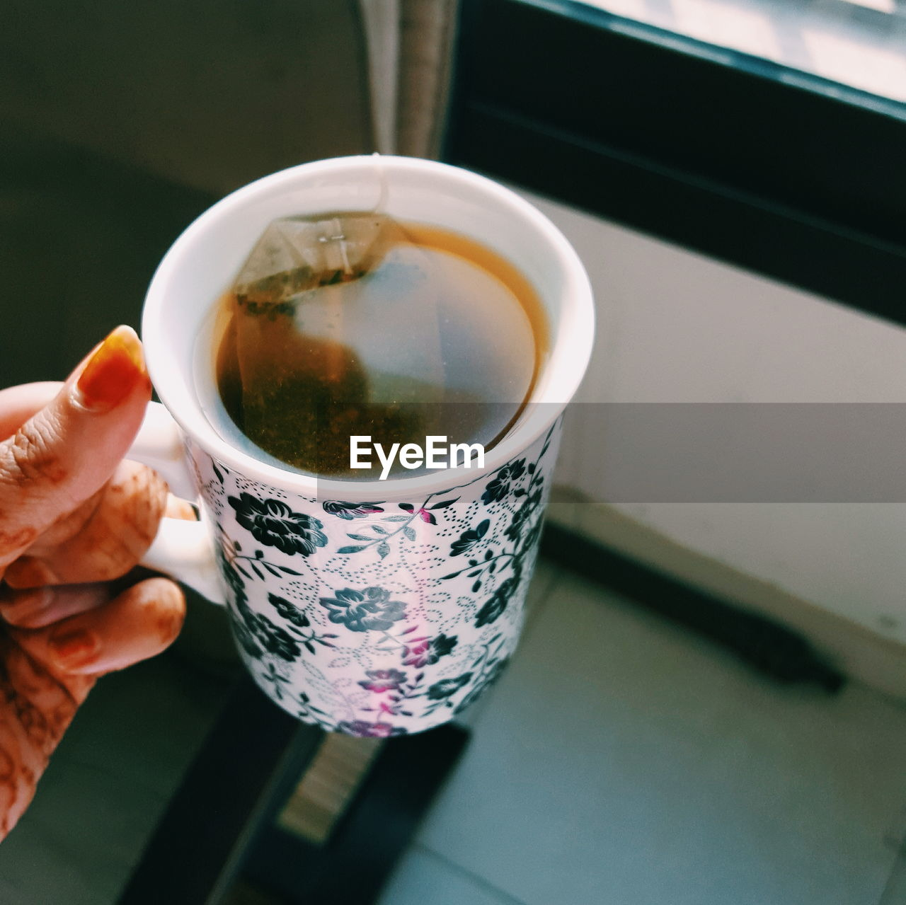 Cropped Hand Of Woman Holding Tea Cup At Home
