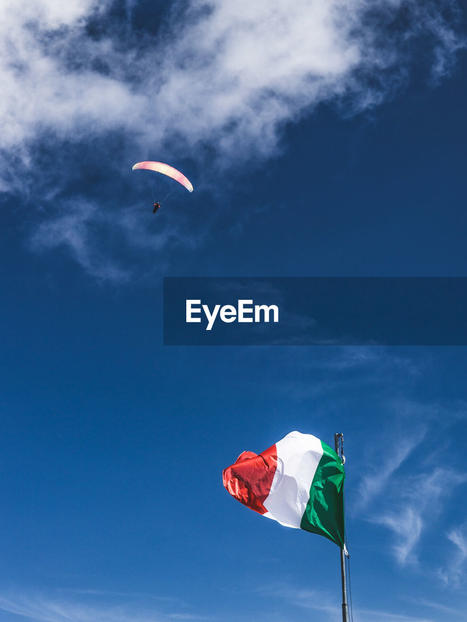 sky, nature, flag, low angle view, sport, day, wind, cloud - sky, environment, leisure activity, parachute, red, lifestyles, flying, unrecognizable person, patriotism, real people, adventure, freedom, outdoors