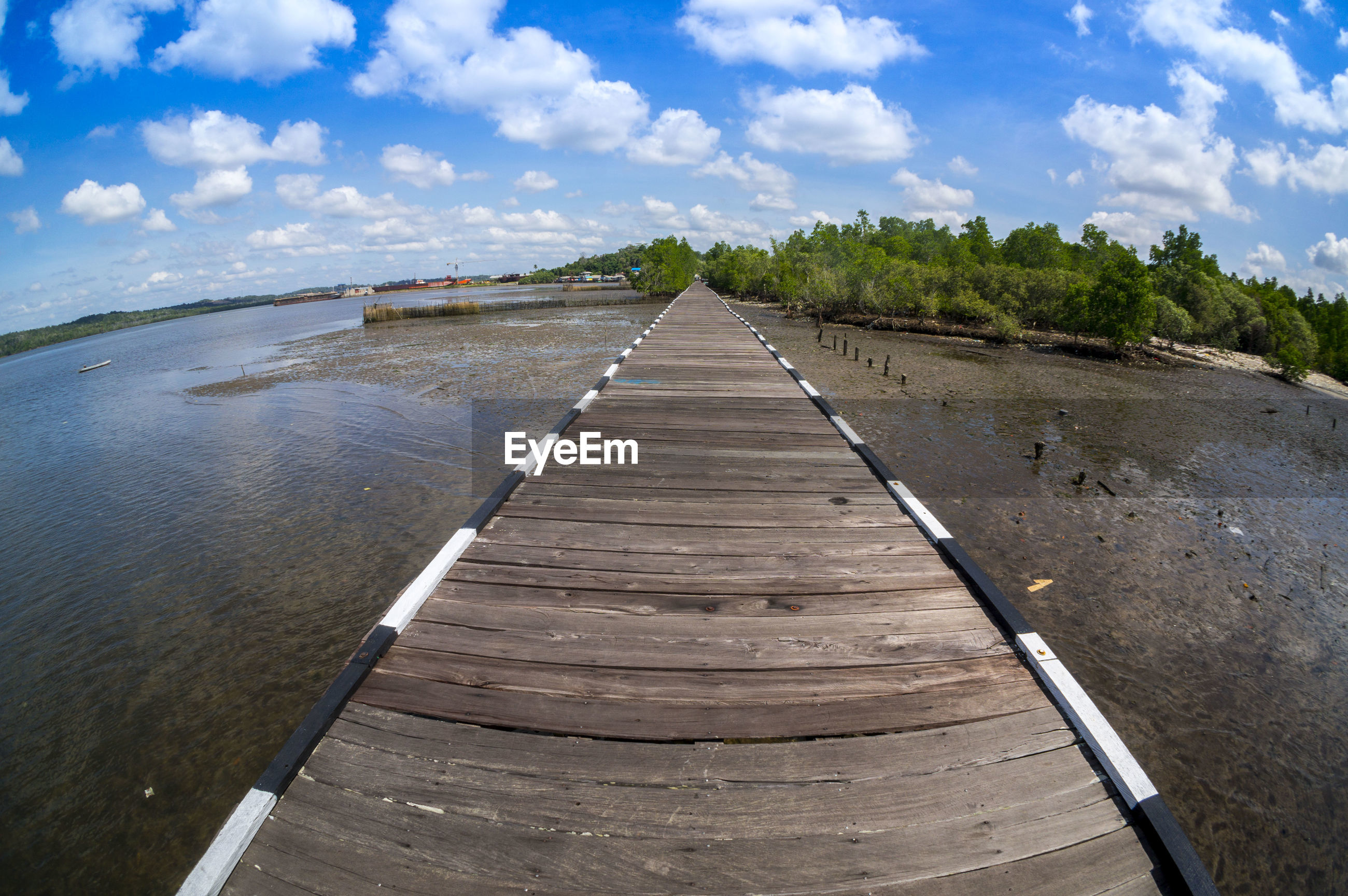 VIEW OF JETTY LEADING TOWARDS WATER AGAINST SKY