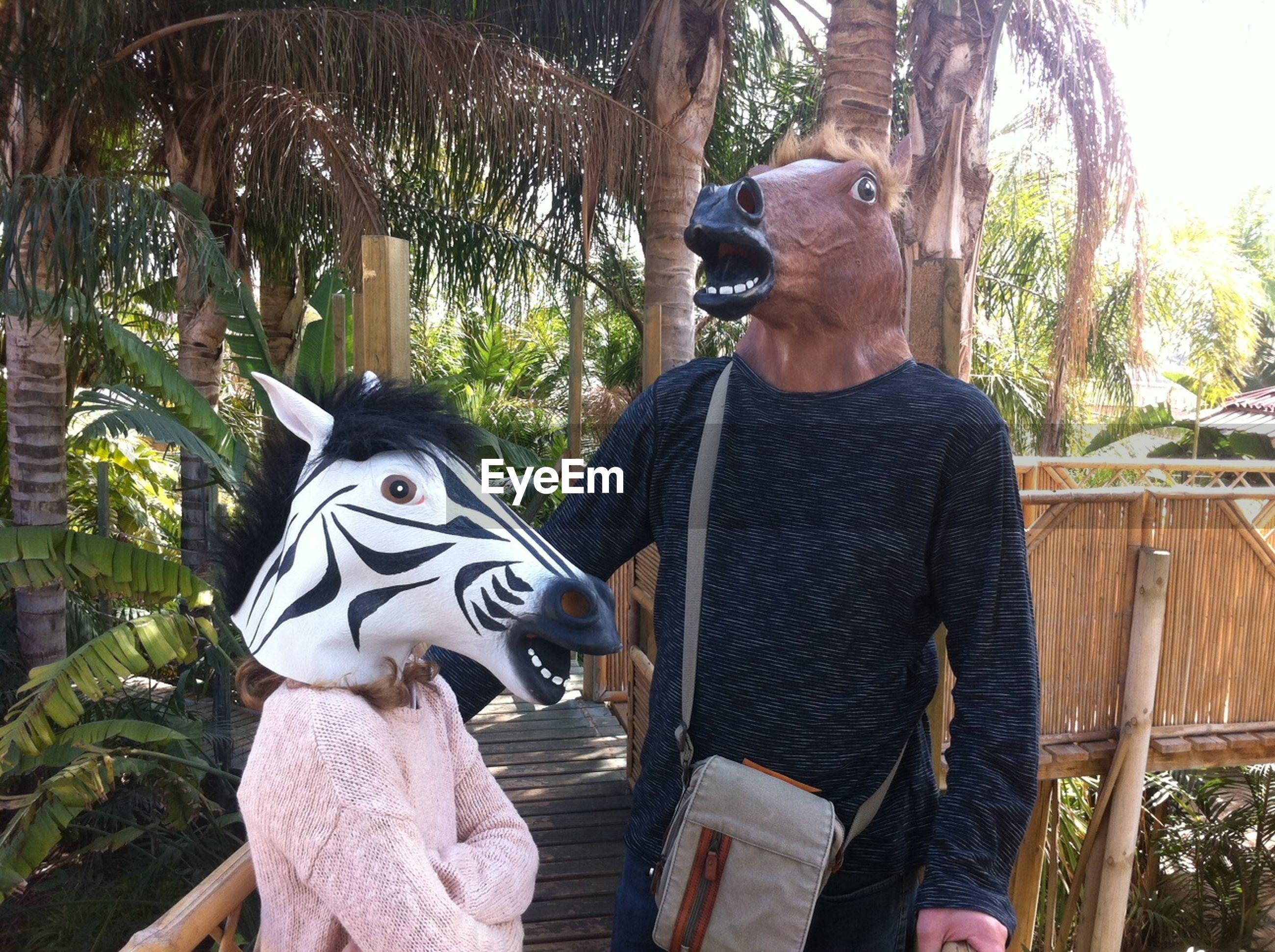 Man and woman in animal masks on footbridge