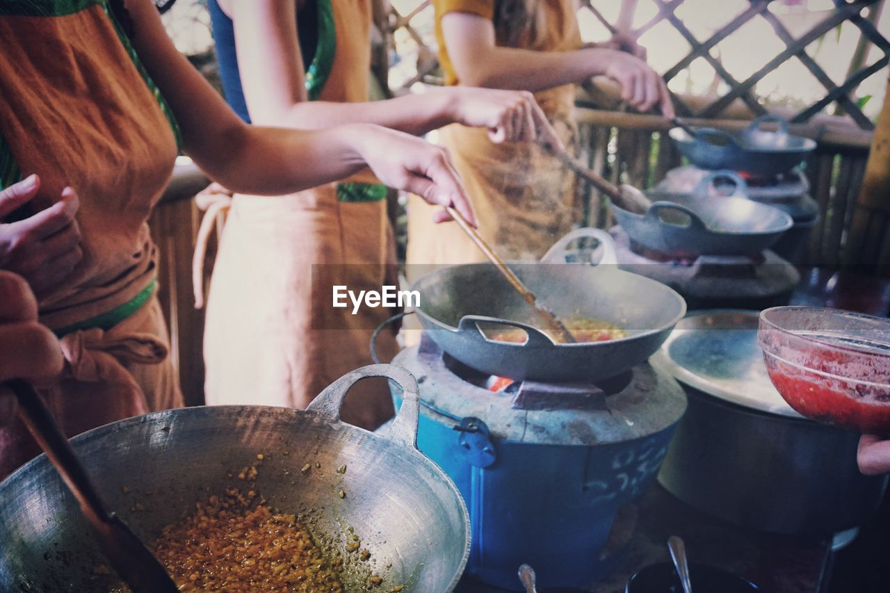heat - temperature, preparation, real people, food, food and drink, container, preparing food, stove, men, human hand, cooking utensil, holding, camping stove, women, indoors, occupation, working, day, healthy eating, freshness, one person, close-up, people