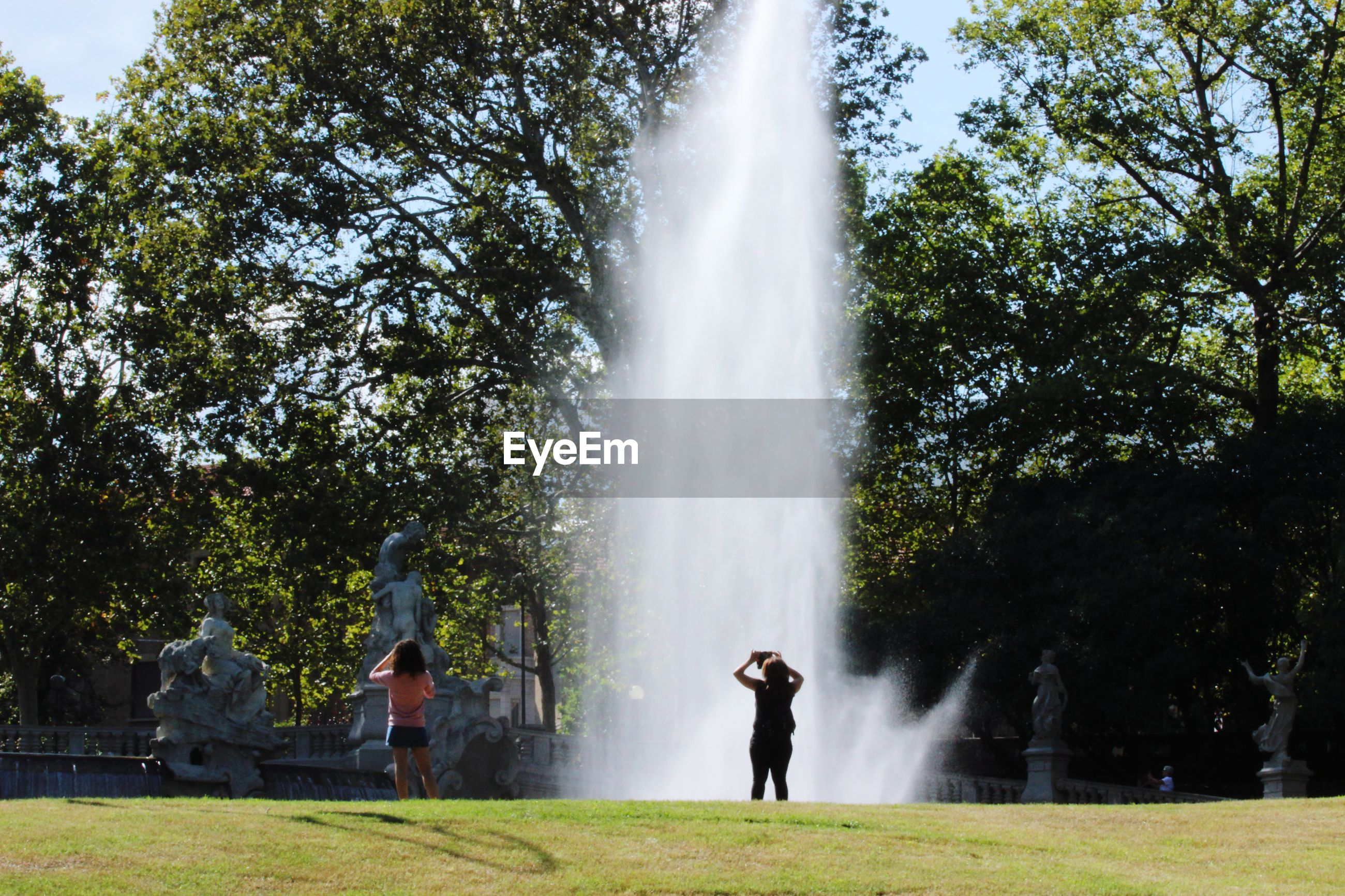 PEOPLE IN PARK AGAINST FOUNTAIN