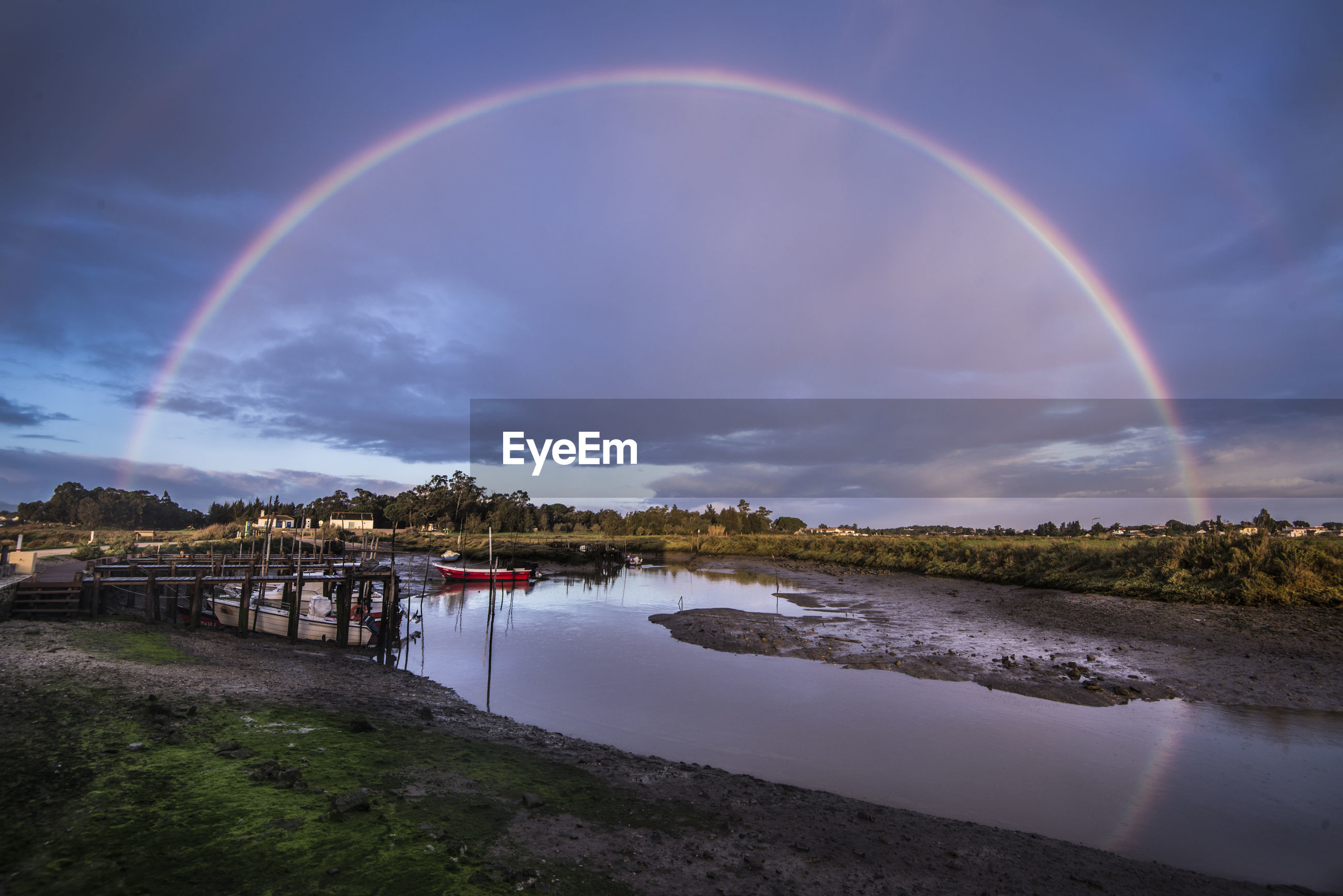 Scenic view of rainbow over river against cloudy sky