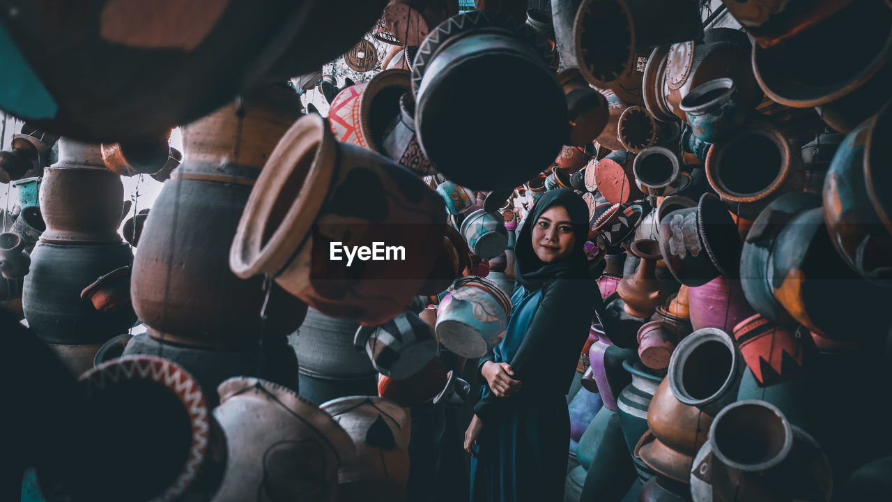 Portrait of woman wearing hijab standing amidst potteries at market