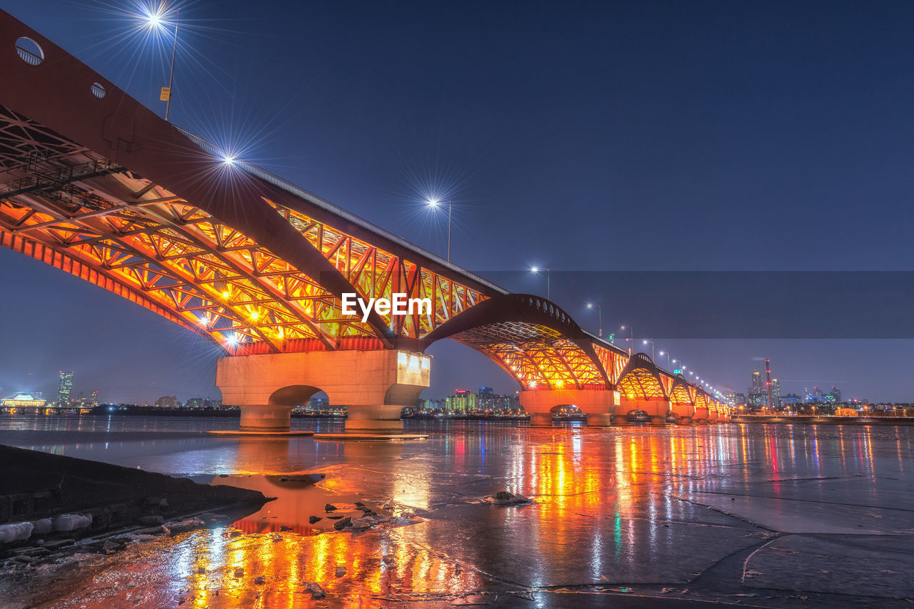 illuminated, connection, architecture, built structure, bridge, transportation, bridge - man made structure, water, night, sky, engineering, nature, river, street light, city, reflection, street, travel destinations, arch, outdoors, arch bridge, long