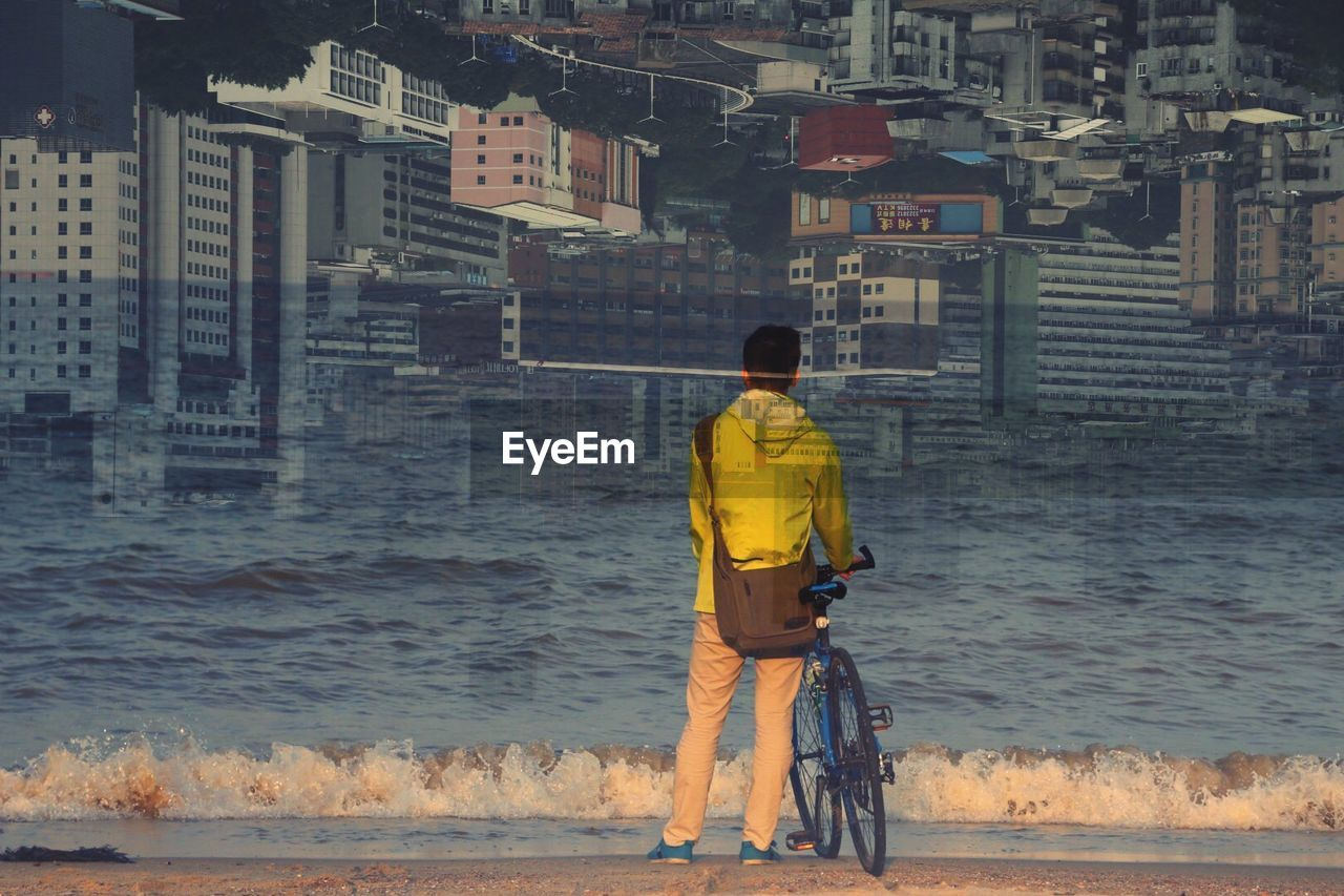 Double Exposure Of Man Standing At Seashore With Cityscape In Background