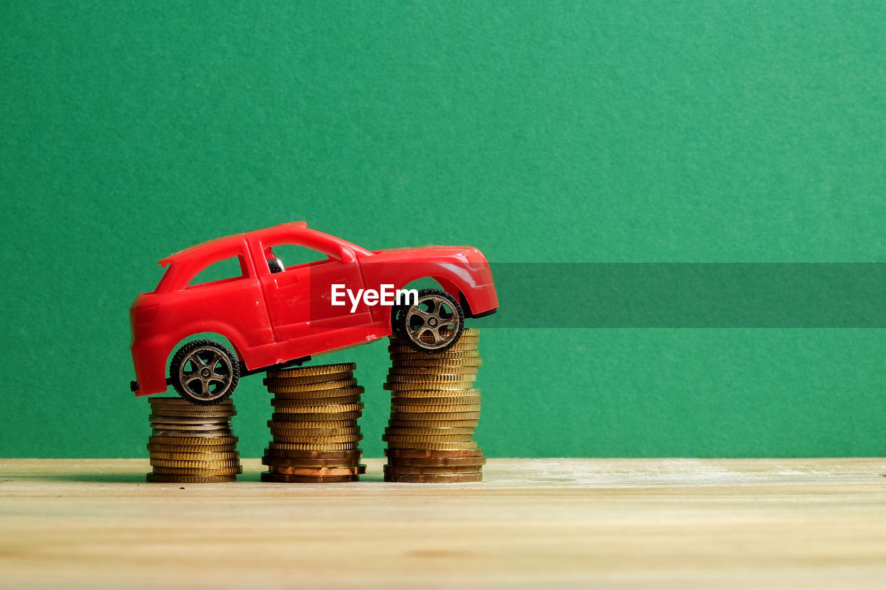 Close-up of toy car on stack of coins against green wall