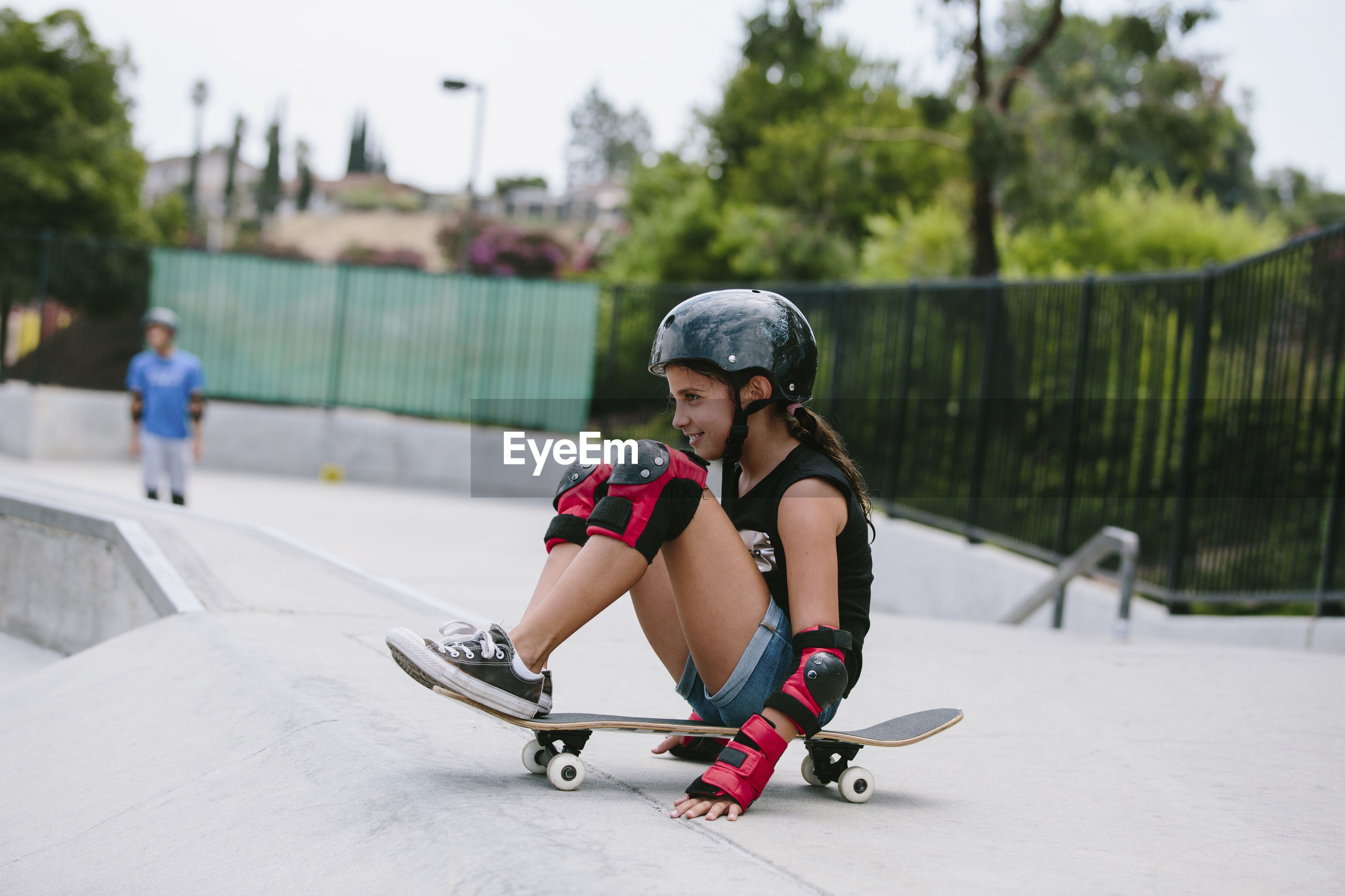 HIGH ANGLE VIEW OF WOMAN AND SKATEBOARD ON STREET