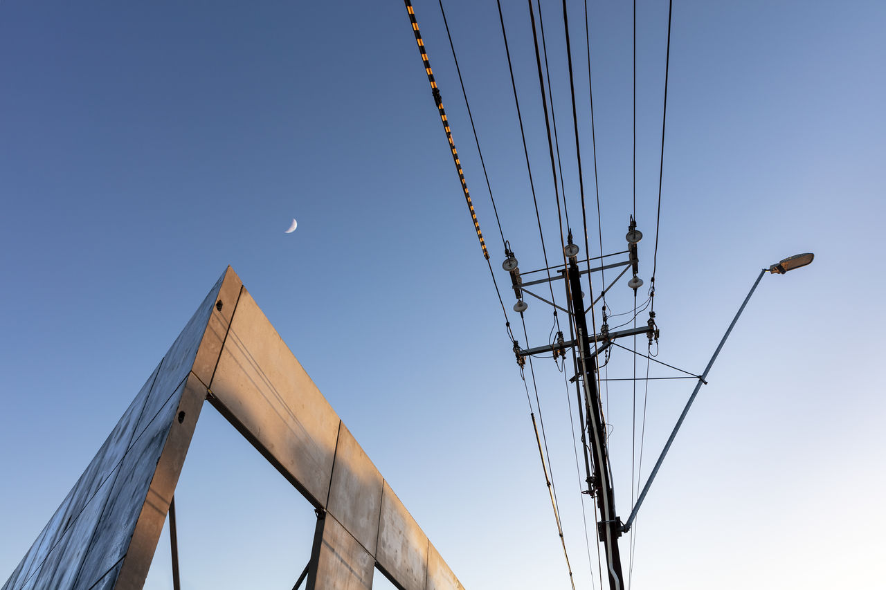sky, low angle view, connection, cable, clear sky, no people, power line, nature, electricity, blue, technology, day, outdoors, power supply, built structure, fuel and power generation, electricity pylon, architecture, copy space, lighting equipment, sailboat, telephone line