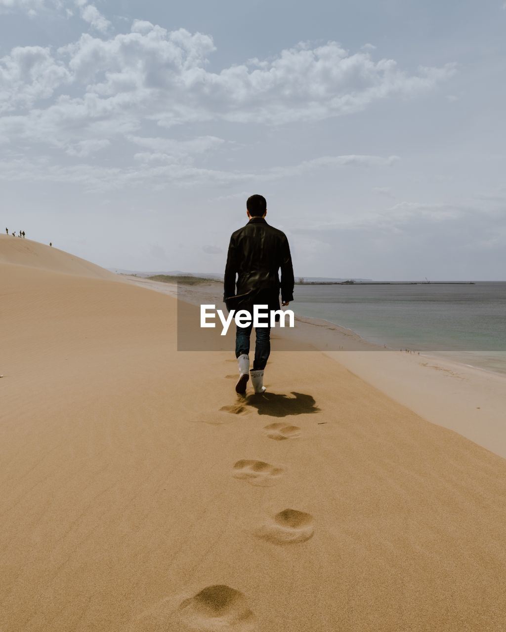 Rear view of man walking on sand dune by beach