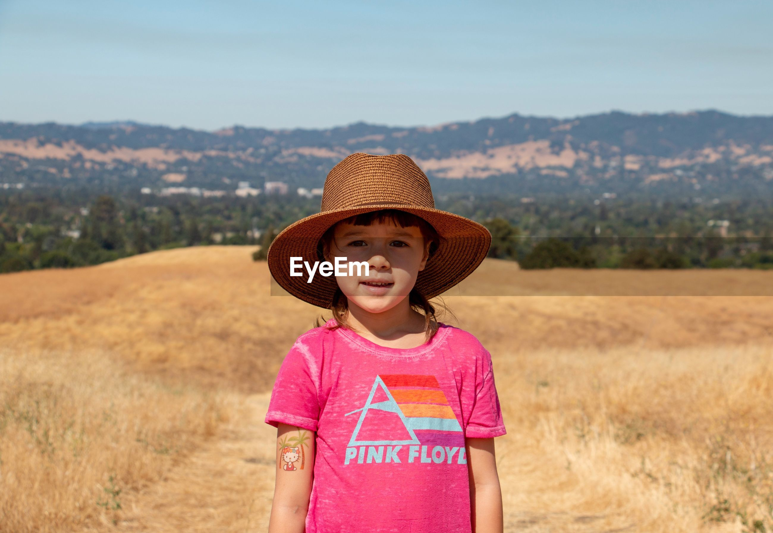 Portrait of cute smiling girl wearing hat standing on field during summer